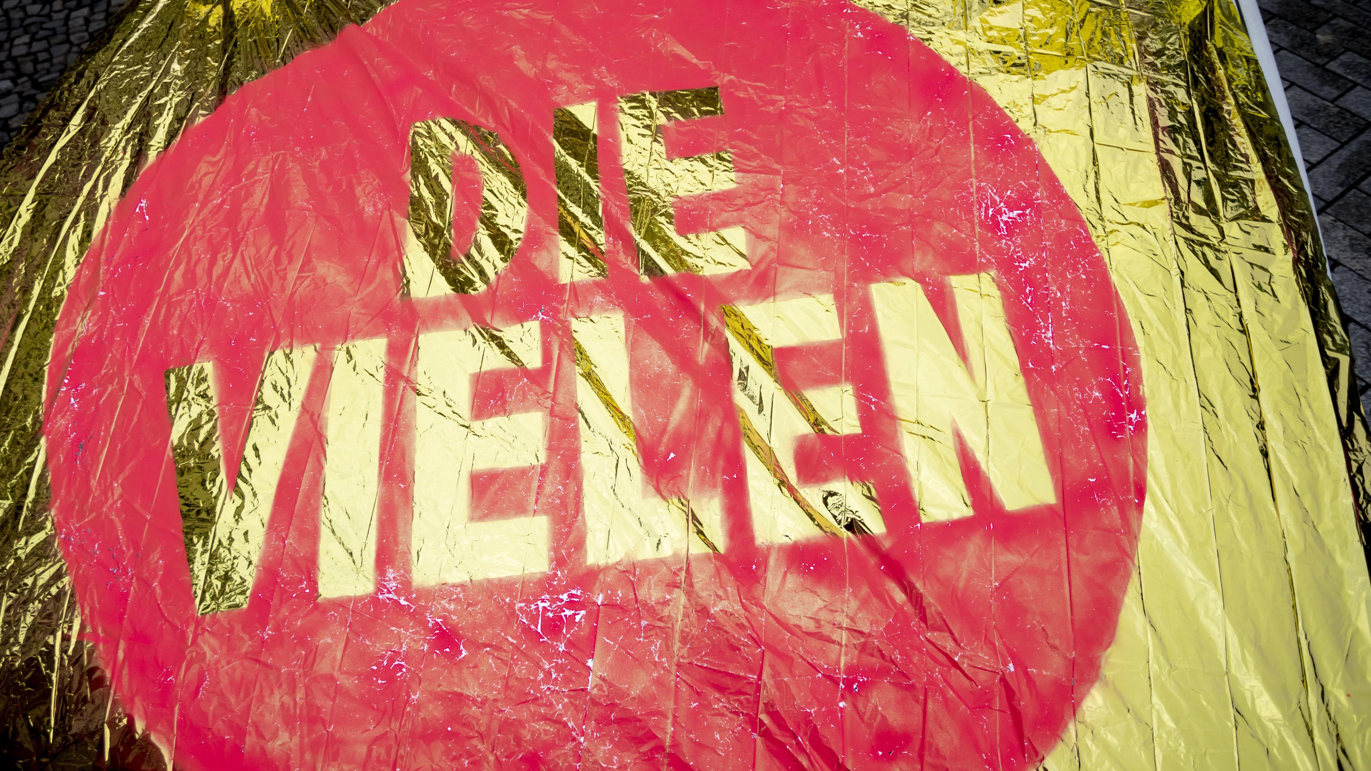 """Die Flagge der Initiative """"Die Vielen"""": Sie ist golden und hat einen roten Kreis mit der Aufschrift """"Die Vielen""""."""