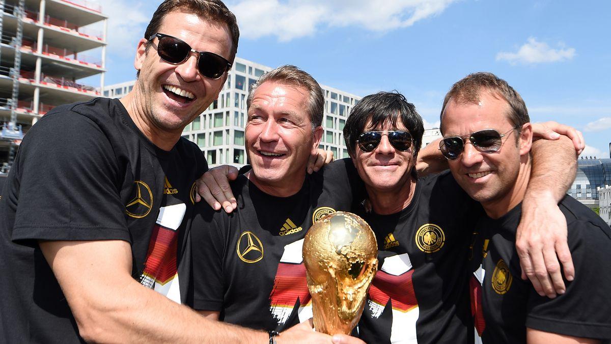 Oliver Bierhoff, Andreas Köpcke, Bundestrainer Joachim Löw und Hansi Flick mit dem WM-Pokal auf der Fan-Meile in Berlin.