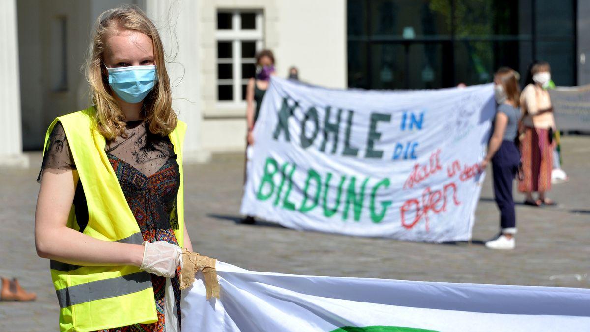 """Archivbild: Oldenburg: Aktivisten der Klimabewegung """"Fridays for Future"""" stehen mit Transparenten auf dem Schlossplatz."""