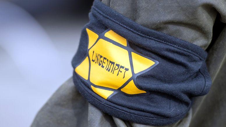 """Bei einer Demonstration gegen die Einschränkungen durch die Corona-Maßnahmen trägt ein Teilnehmer eine Armbinde mit der Aufschrift """"Ungeimpft"""".   Bild:picture alliance/dpa/Christophe Gateau"""