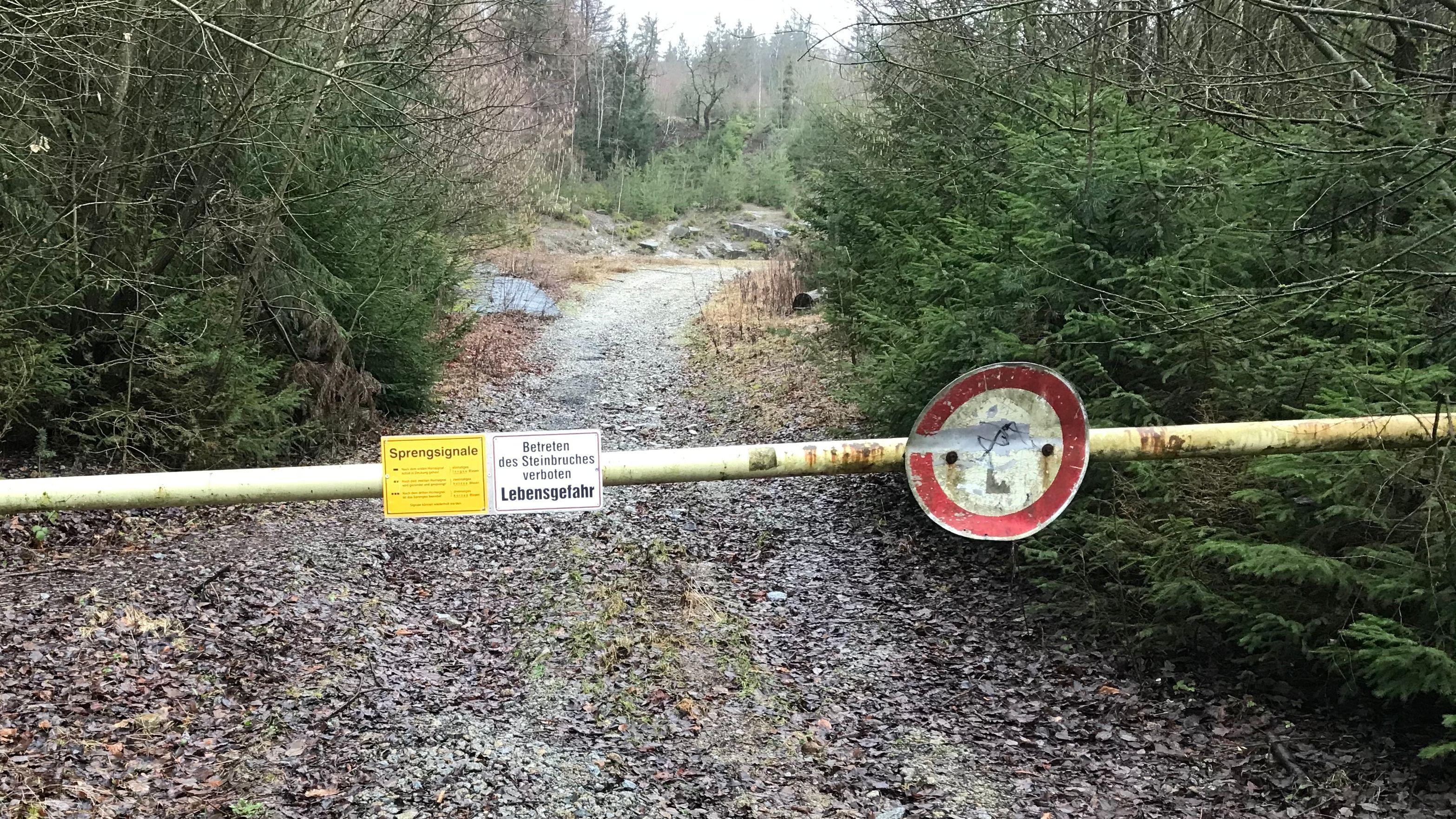 Eine Schranke vor einem Waldweg.