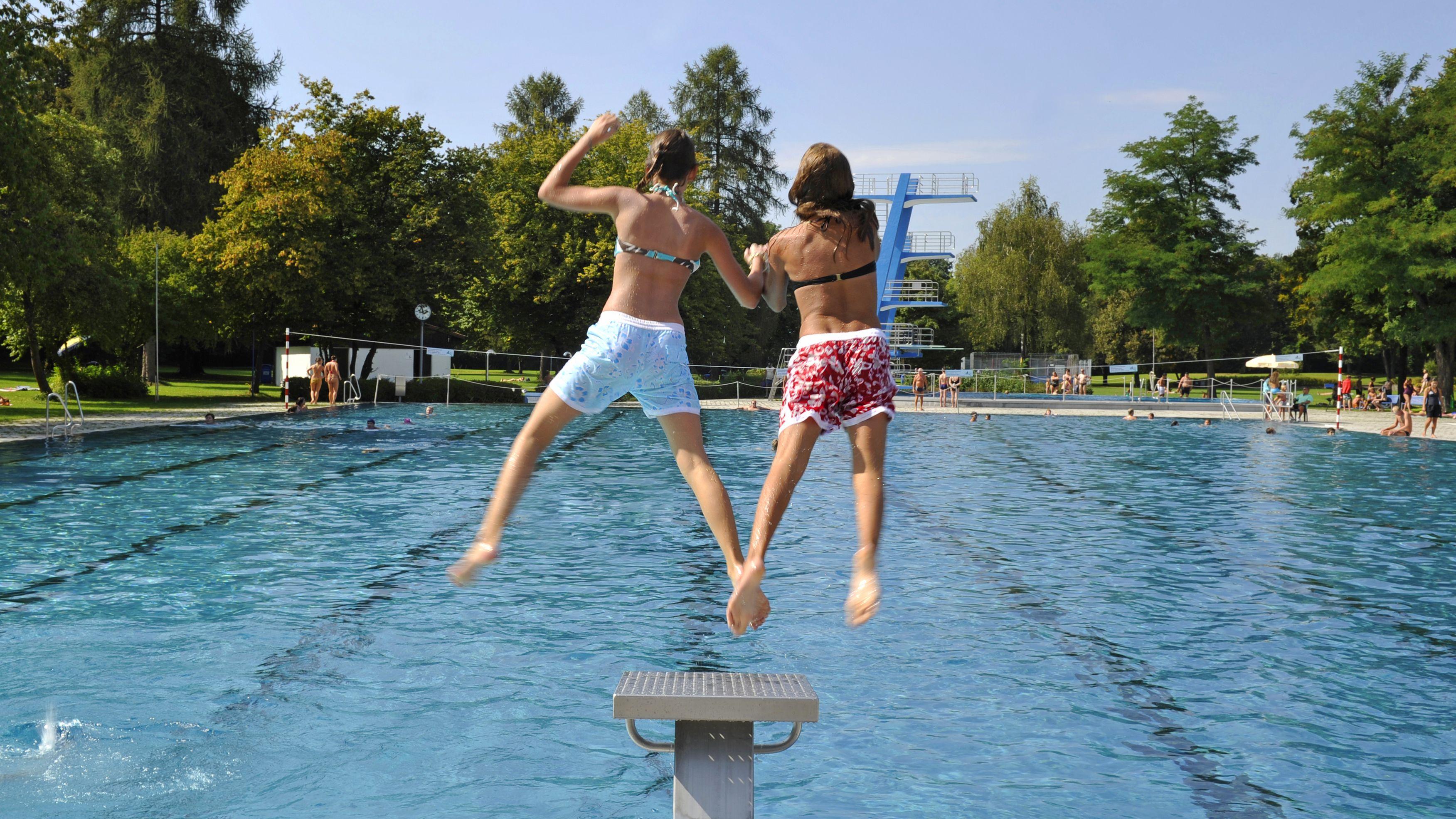 Zwei Mädchen springen ins Michaelibad in München