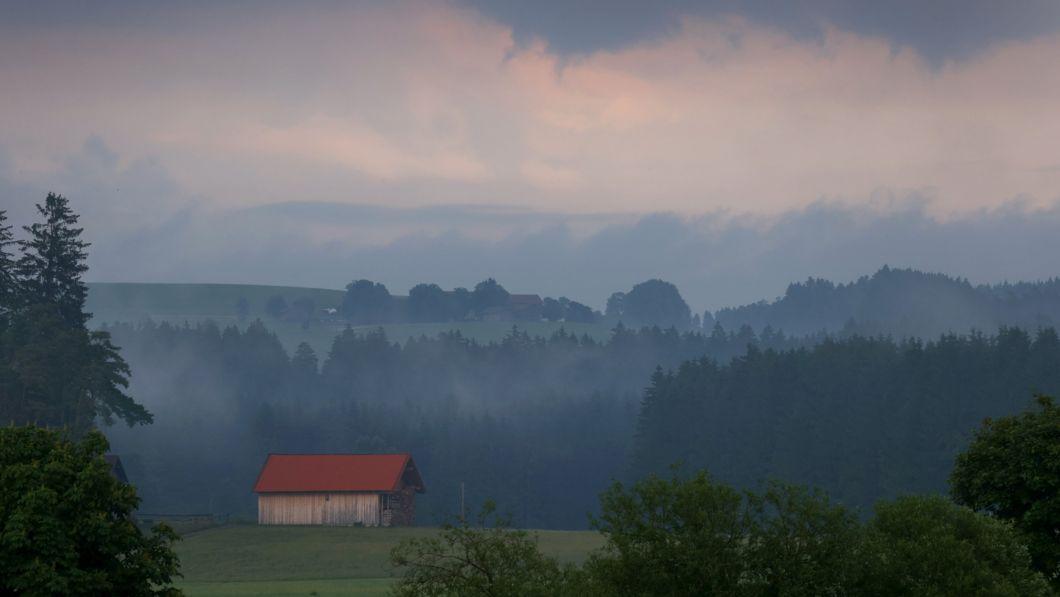 22.06.2021, Bayern, Marktoberdorf: Eine Holzhütte steht im Abendlicht in der wolkenverhangenen Allgäuer Landschaft.