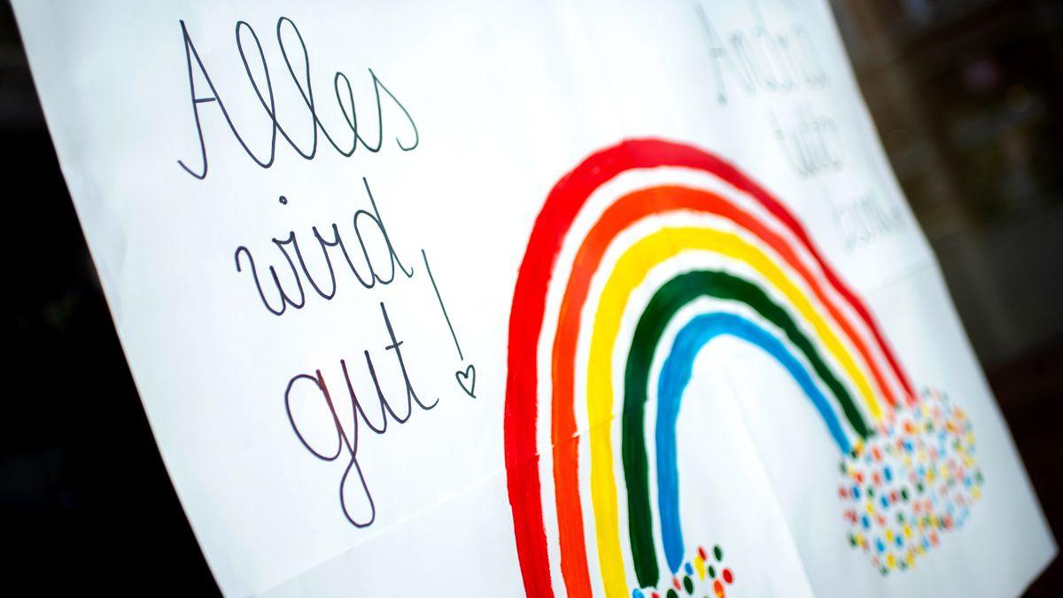 """Schild mit Regenbogen und """"Alles wird gut!""""-Aufschrift."""