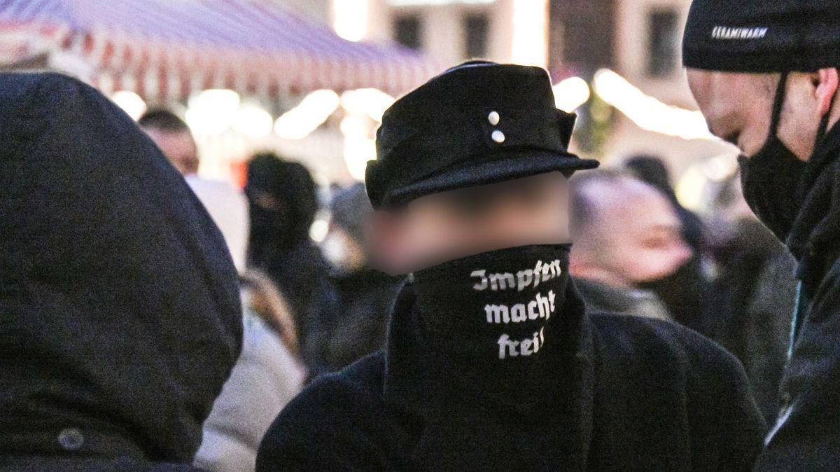 """Ein Mann mit schwarzer Schirmmütze trägt eine schwarze Maske mit der Aufschrift """"Impfen macht frei""""."""