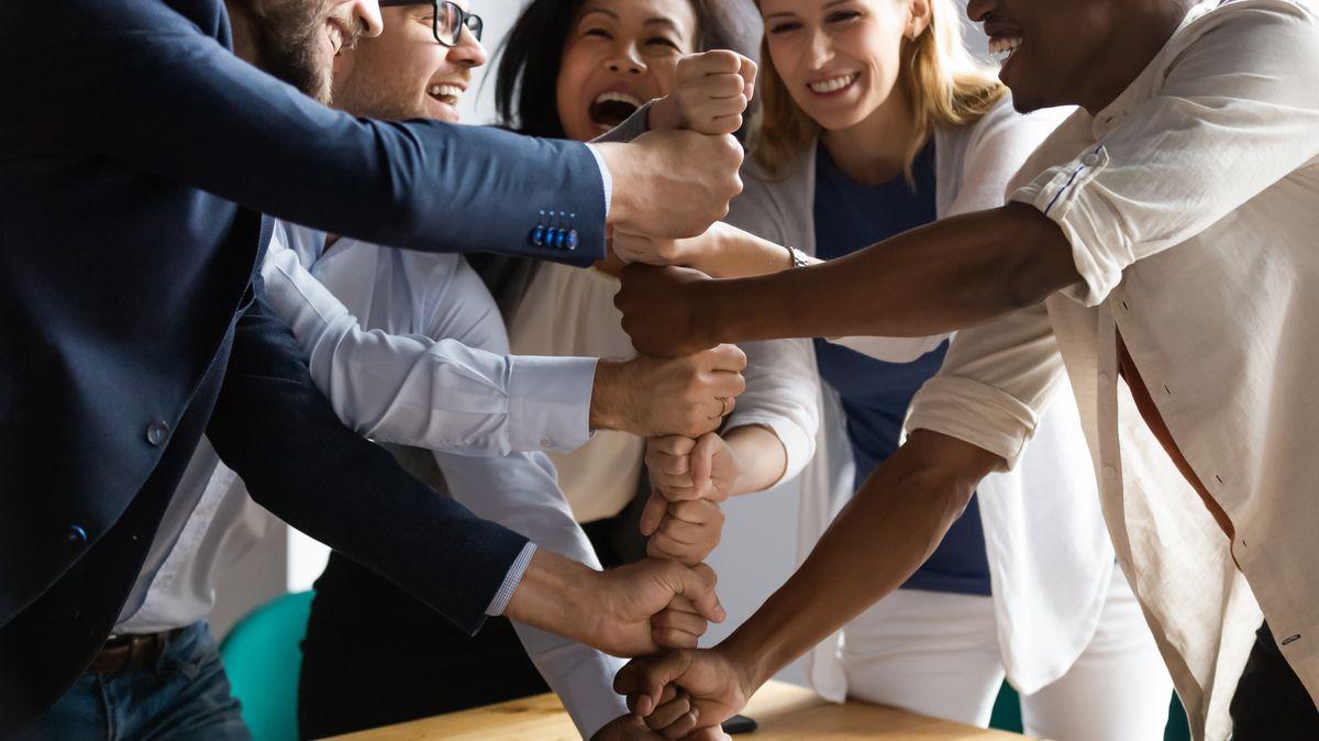 Ein Team aus Arbeitskollegen steht um einen Tisch im Kreis und legt die Fäuste übereinander.