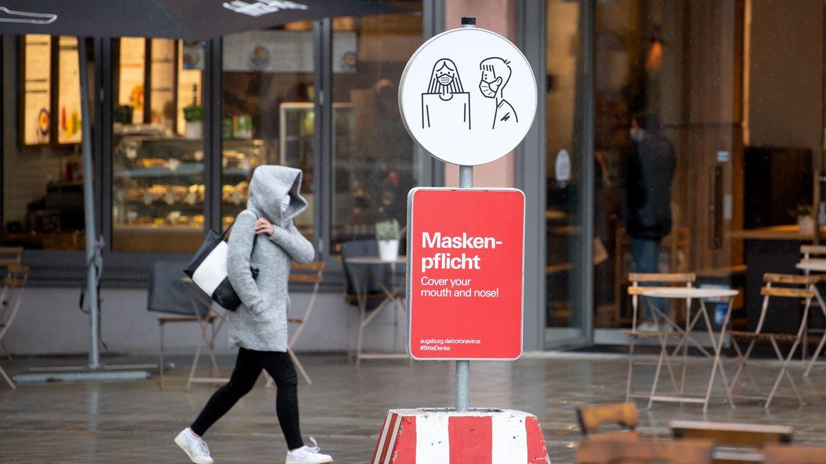 Frau geht in der Augsburger Innenstadt vor einem Hinweisschild zur Maskenpflicht vorbei