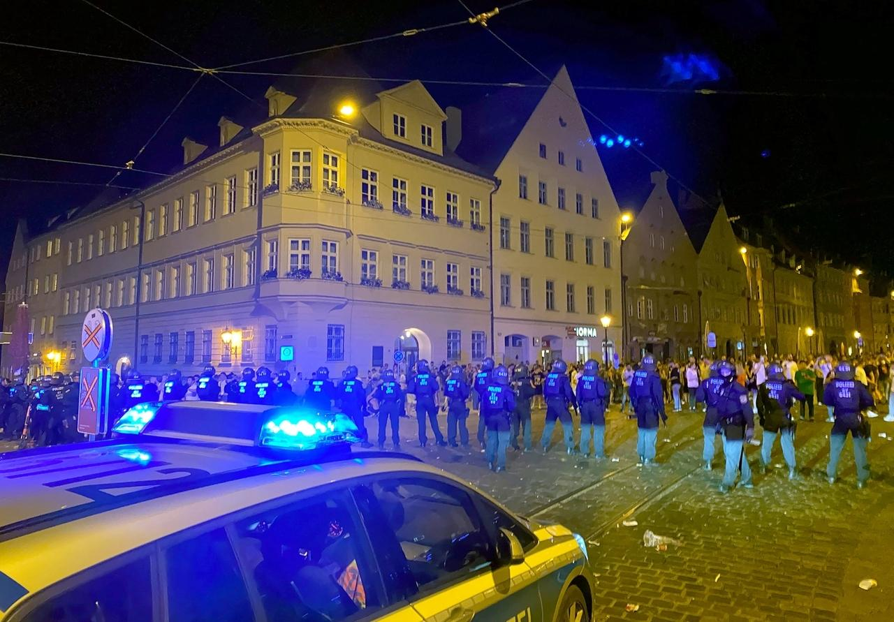 19.06.2020, Bayern, Augsburg: Polizisten stehen an einem Platz in der Innenstadt, wo sich Menschen zum Feiern versammelt haben. Die Polizei hat in der Nacht zu Sonntag eine Ansammlung von hunderten Feiernden aufgelöst. Bei dem Einsatz seien zahlreiche Beamte verletzt worden, sagte ein Polizeisprecher. Auch auf der Seite der Feiernden habe es Verletzte bei dem Einsatz gegeben.