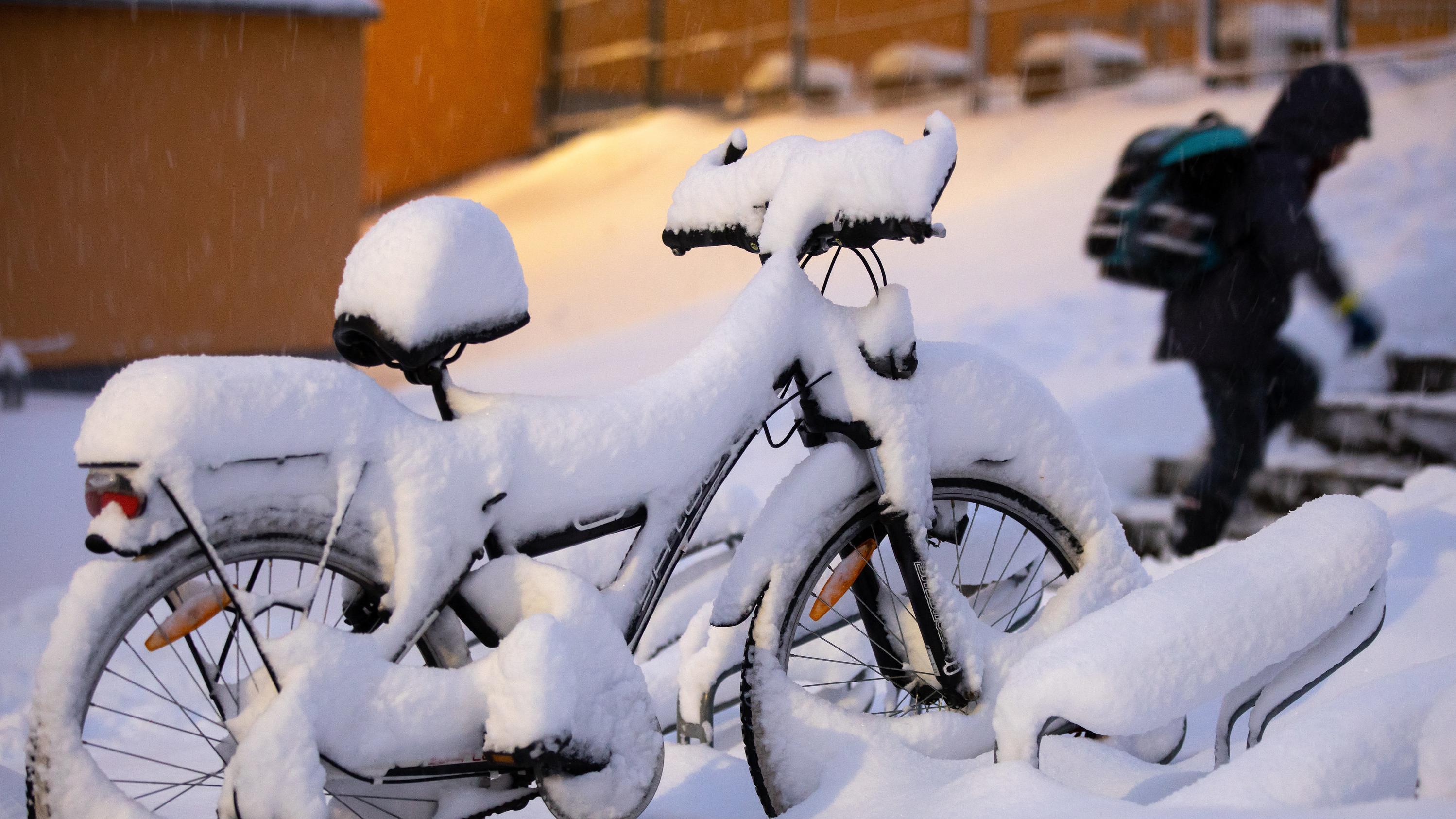 Verschneites Fahrrad und Schulkind