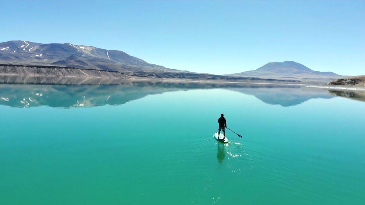 Mann auf Standup-Paddle-Board auf grün-schimmerndem Bergsee