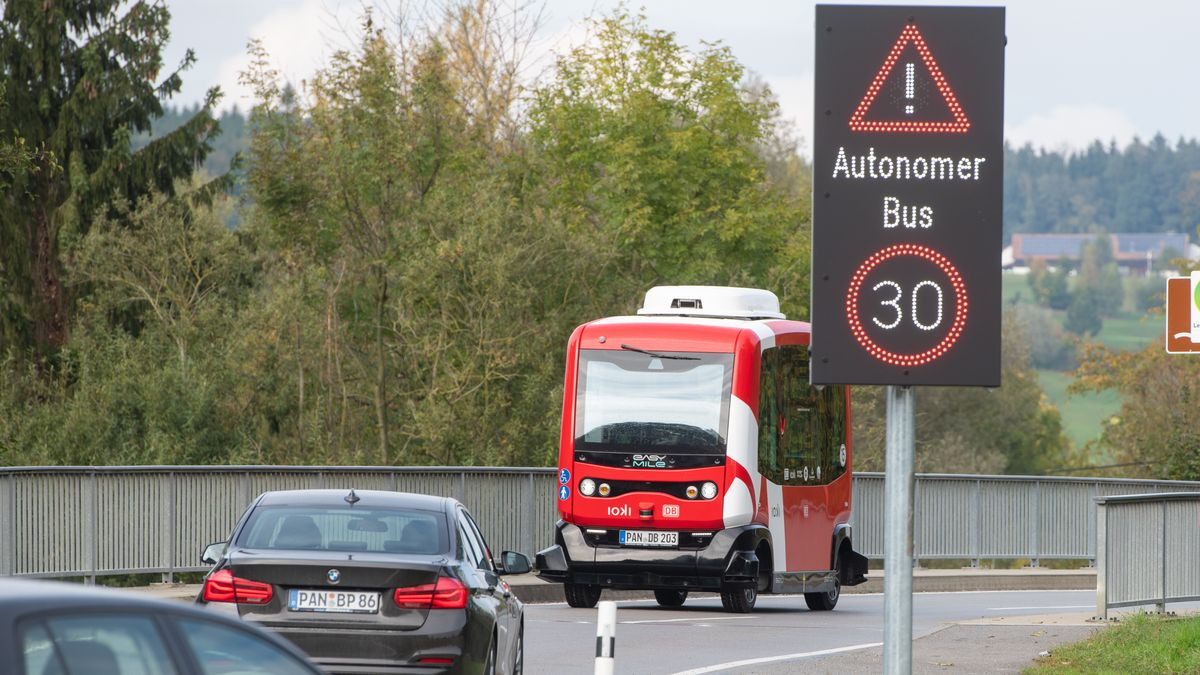 """Ein autonom fahrender Elektrobus fährt im niederbayerischen Bad Birnbach hinter einem Hinweisschild mit der Aufschrift """"Autonomer Bus""""."""