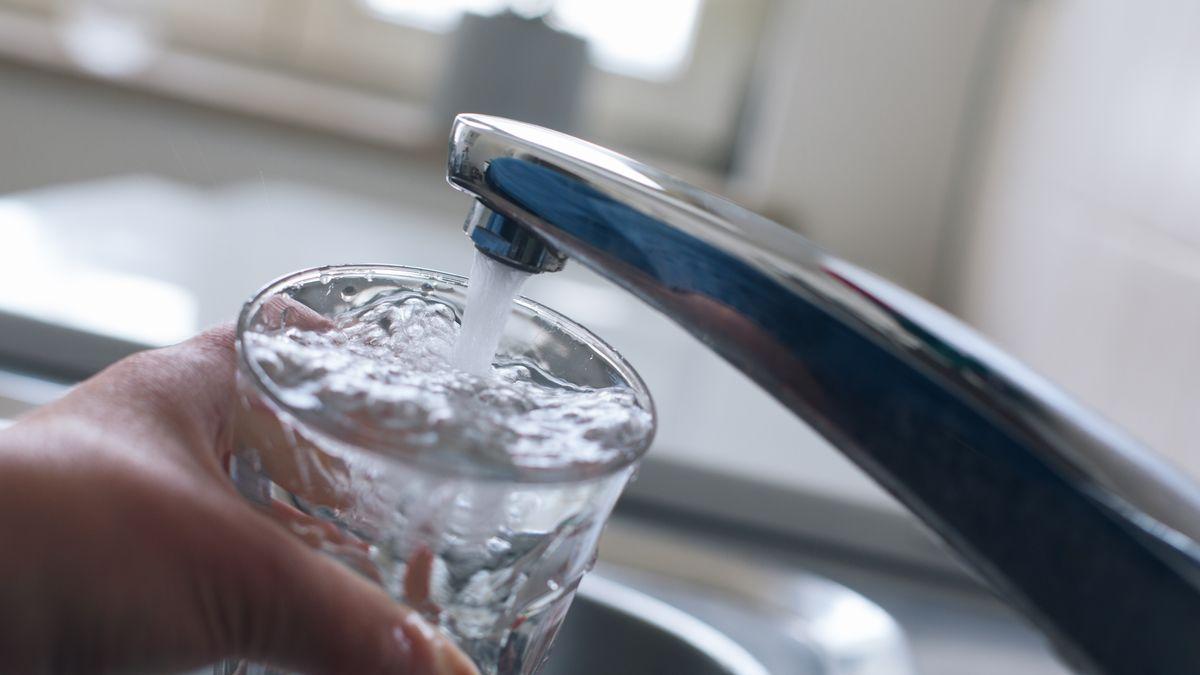 Jemand füllt am Wasserhahn ein Glas mit Leitungswasser.