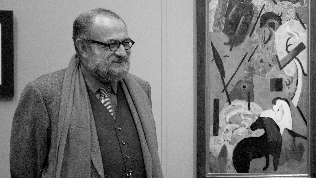 Ein Mann mit Bart steht vor einem Gemälde