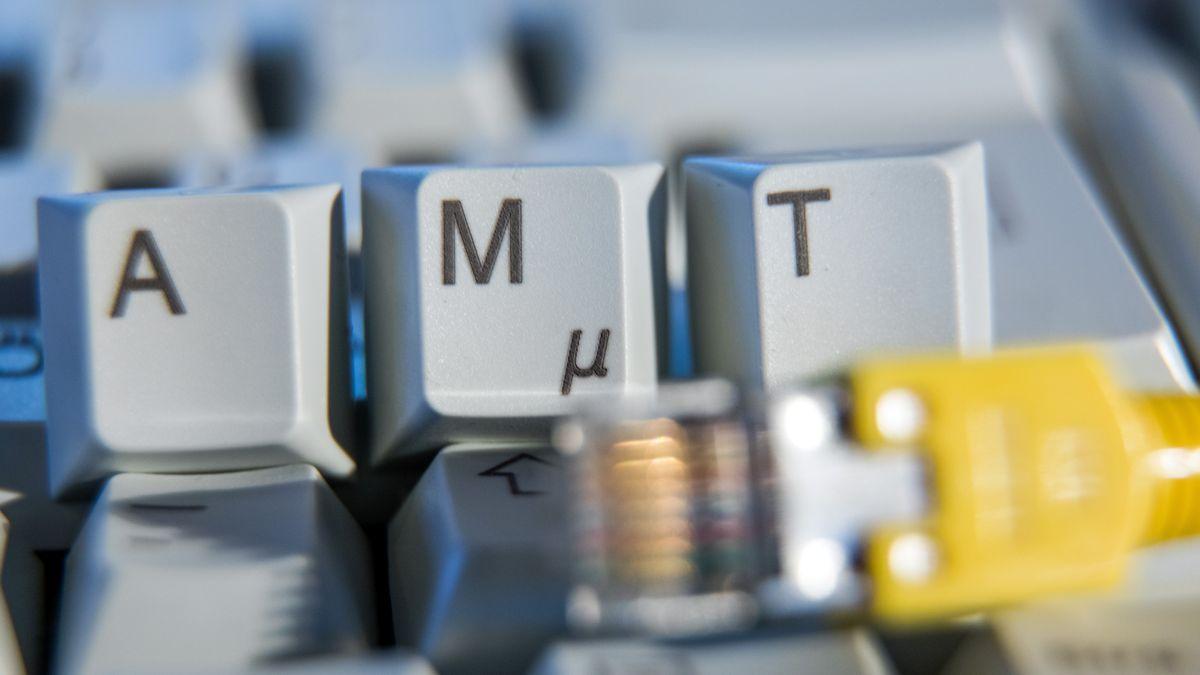 """Schriftzug """"Amt"""" auf einer Computertastatur hinter einem Netzwerkkabel"""