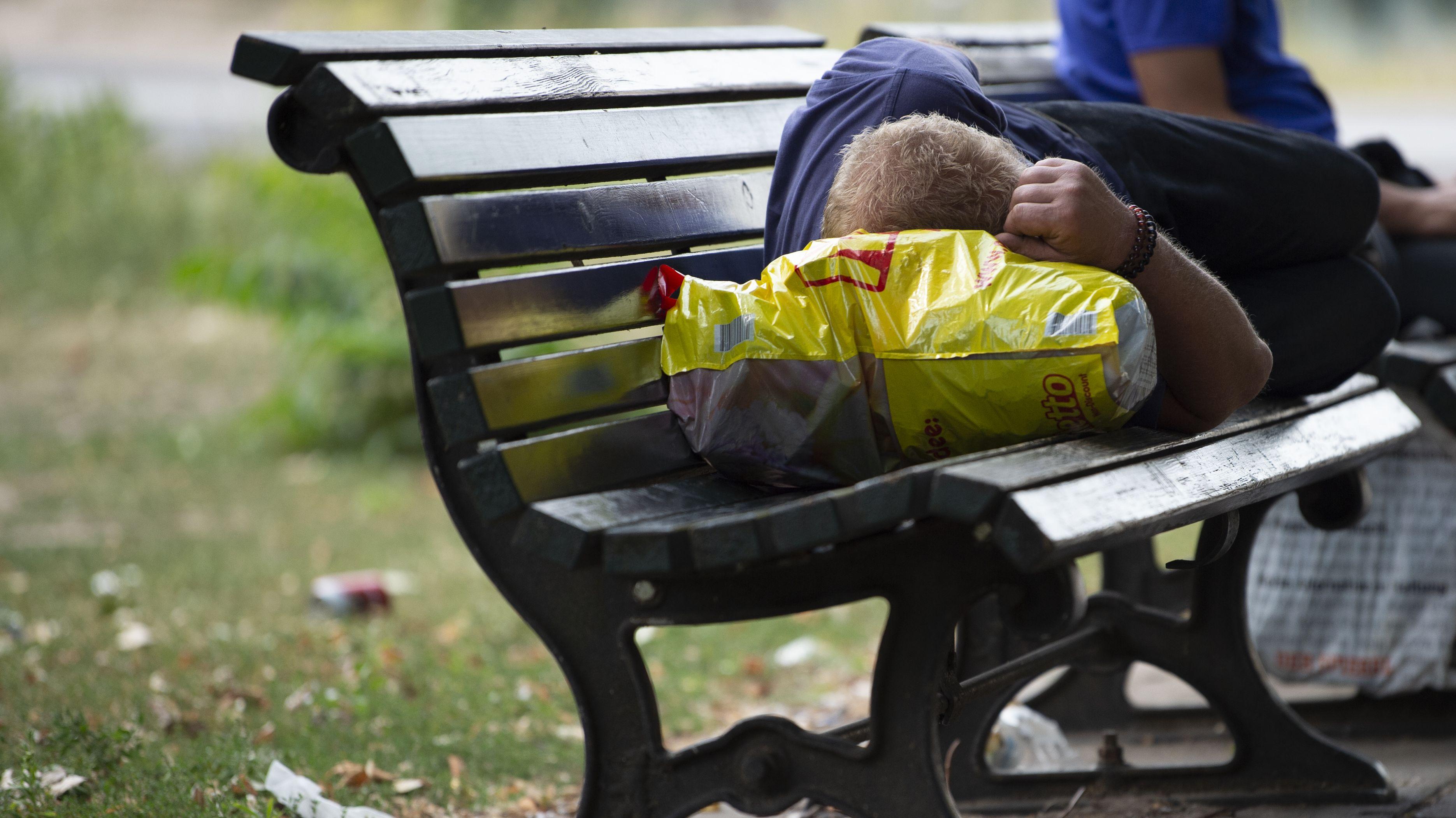 Ein Obdachloser liegt auf einer Parkbank.