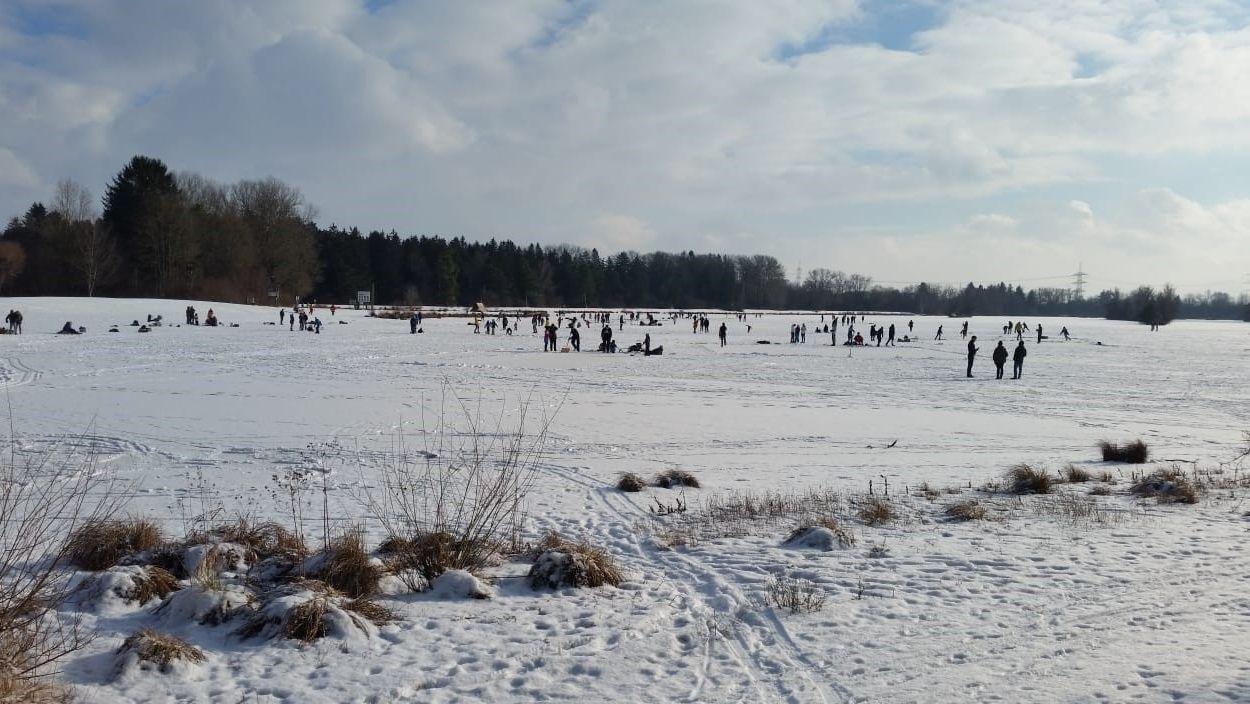 Menschen auf dem verschneiten Weitmannsee