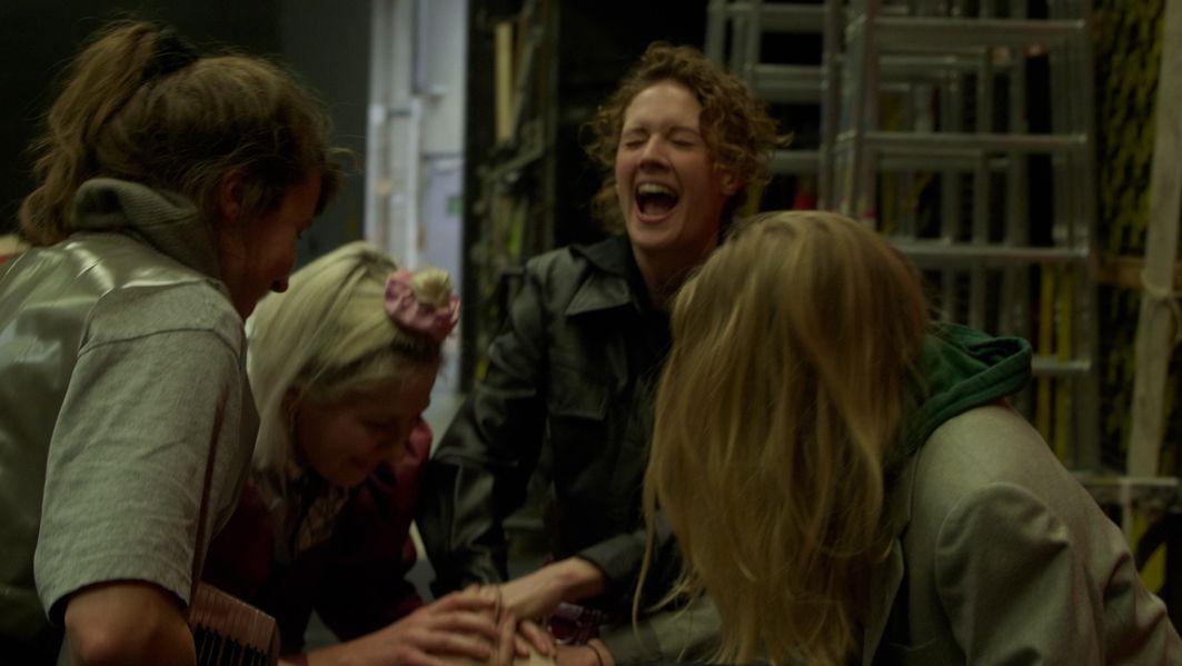 """Vier lachende Frauen in einer dunklen Altbauwohnung türmen ihre Hände aufeinander: : Gro Swantje Kohlhof, Leonie Böhm, Julia Riedler, Eva Löbau und Sophie Krauss bei den Proben zu """"Räuberinnen""""."""