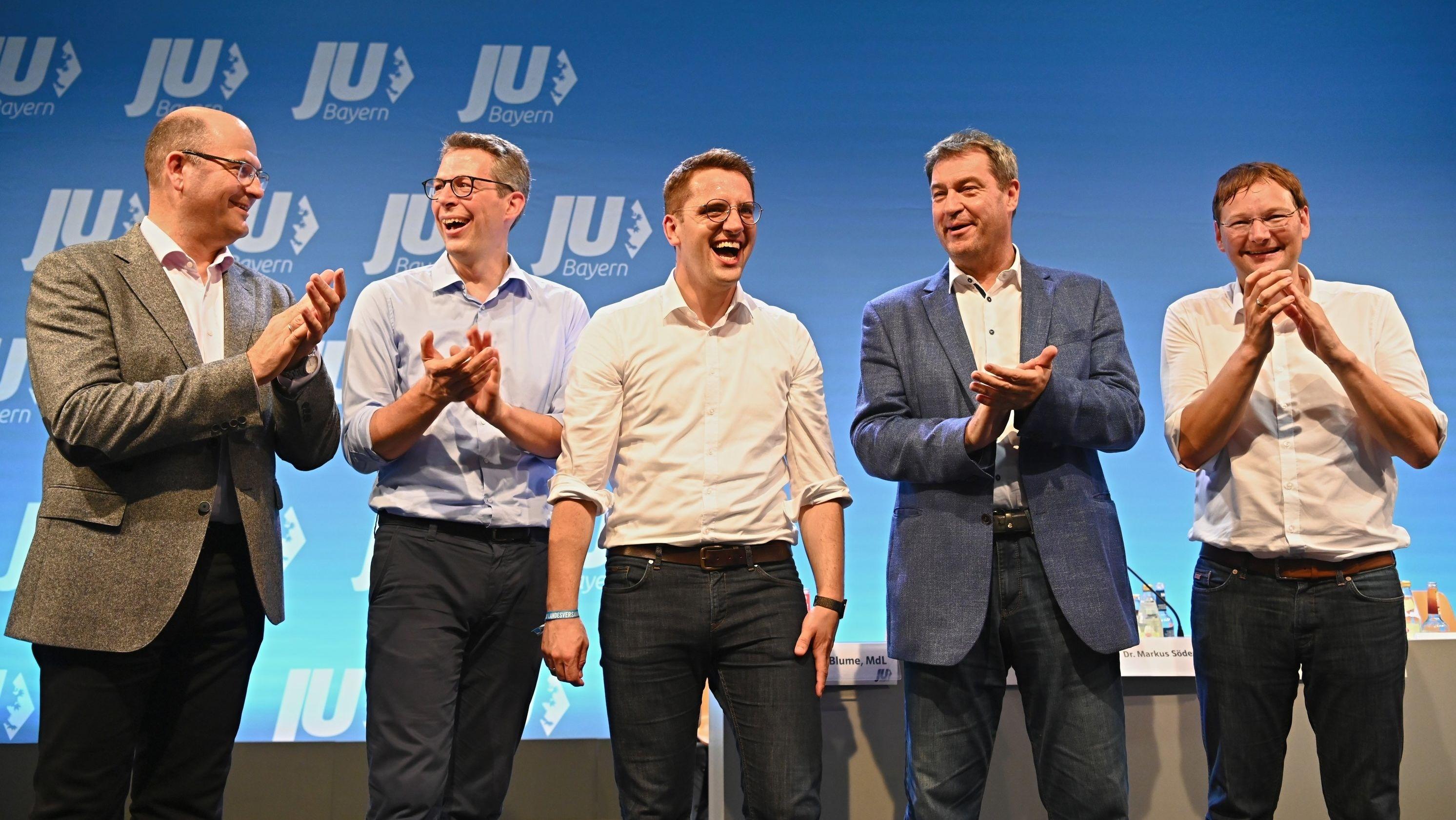 Der als neuer JU-Landeschef gewählte Europaparlamentarier Doleschal (M) wird von Finanzminister Füracker (l), dem Generalsekretär der CSU Blume (2.v.l.), dem bayerischen Ministerpräsidenten (2.v.r.) und dem nun ehemaligen JU-Landesvorsitzenden Reichart (r) zur Wahl applaudiert.