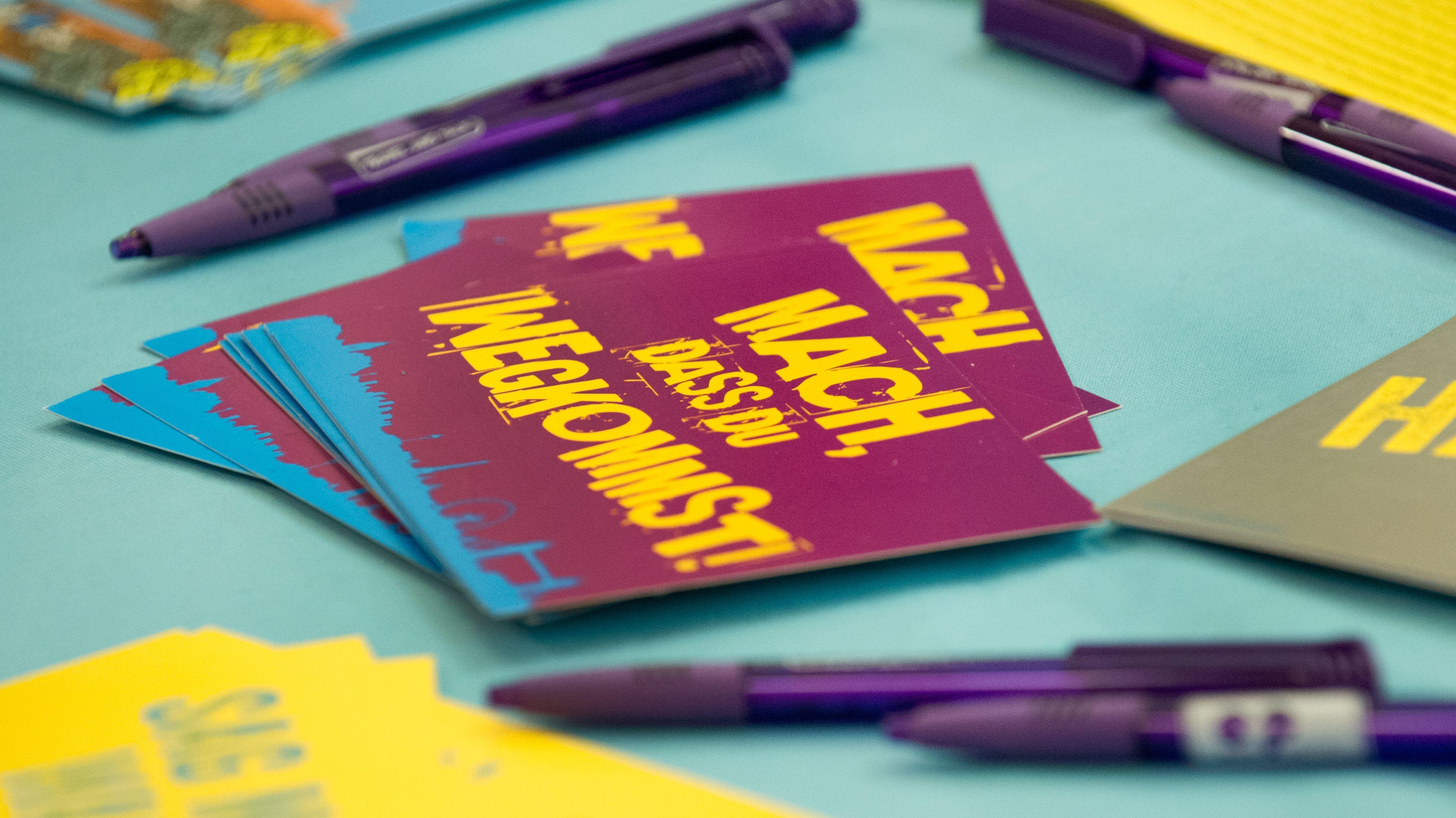 """Eine Postkarte mit der Aufschrift """"Mach, dass du wegkommst!"""" bei einer  Schüler-Austausch-Messe"""