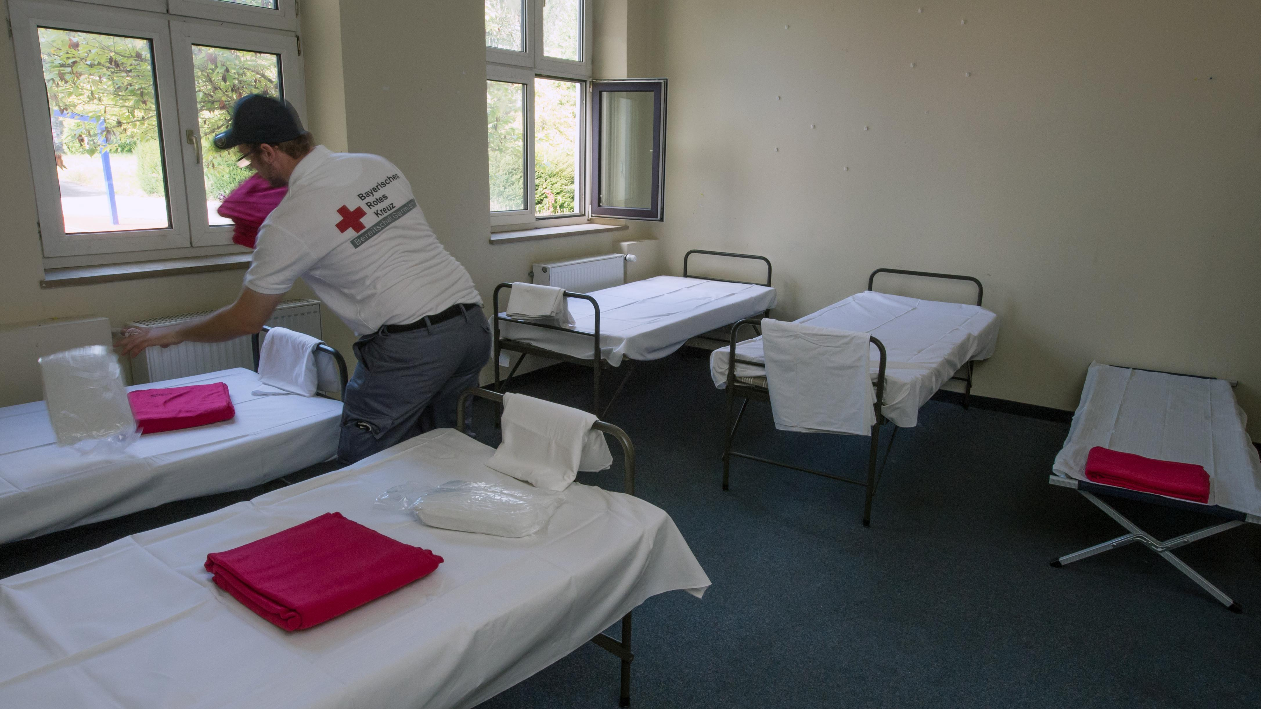 """Helfer des BRK richten am 3.10.2014 in der ehemalige US-Kaserne """"General-Abrams-Complex"""" in Garmisch-Patenkirchen eine Notunterkunft für rund 300 Flüchtlinge ein."""