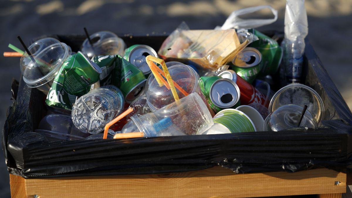 Abfalleimer mit Müll aus Plastikbechern und Dosen