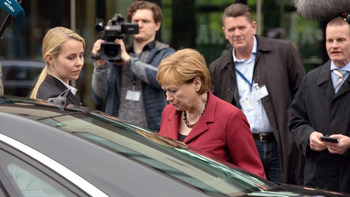 """Eine Frau in einem roten Blazer steigt in eine schwarze Limousine, sie ist umringt von Presse. Still aus dem Film """"Die Getriebenen""""."""