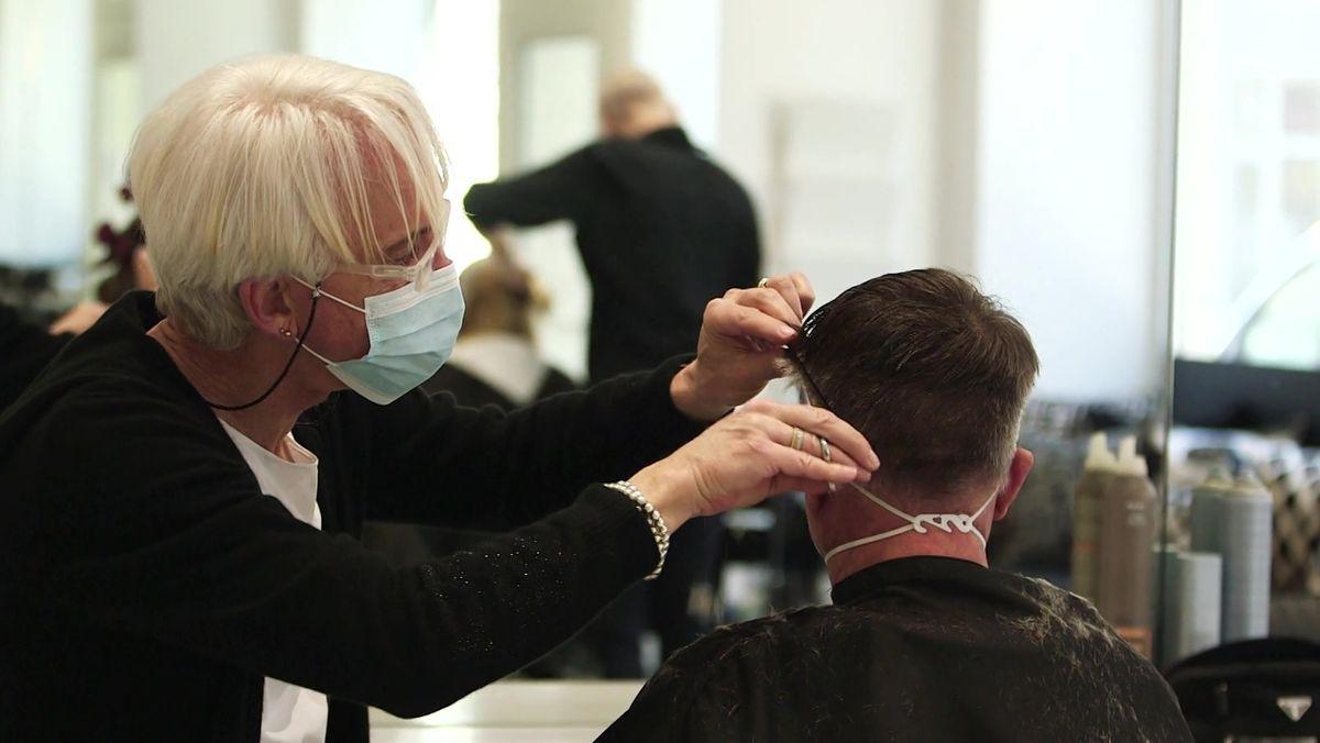 Friseurin schneidet einem Kunden die Haare, beide tragen Masken