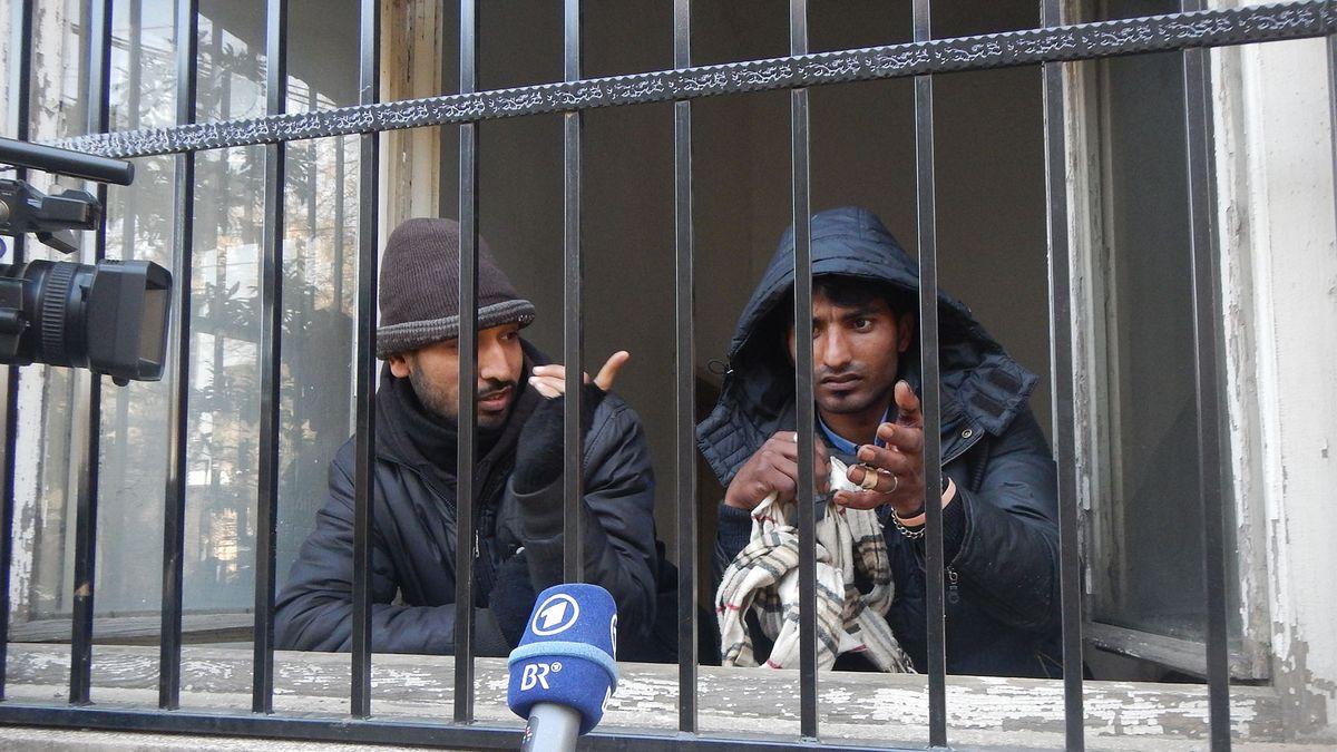 Zwei Männern hinter Gittern.