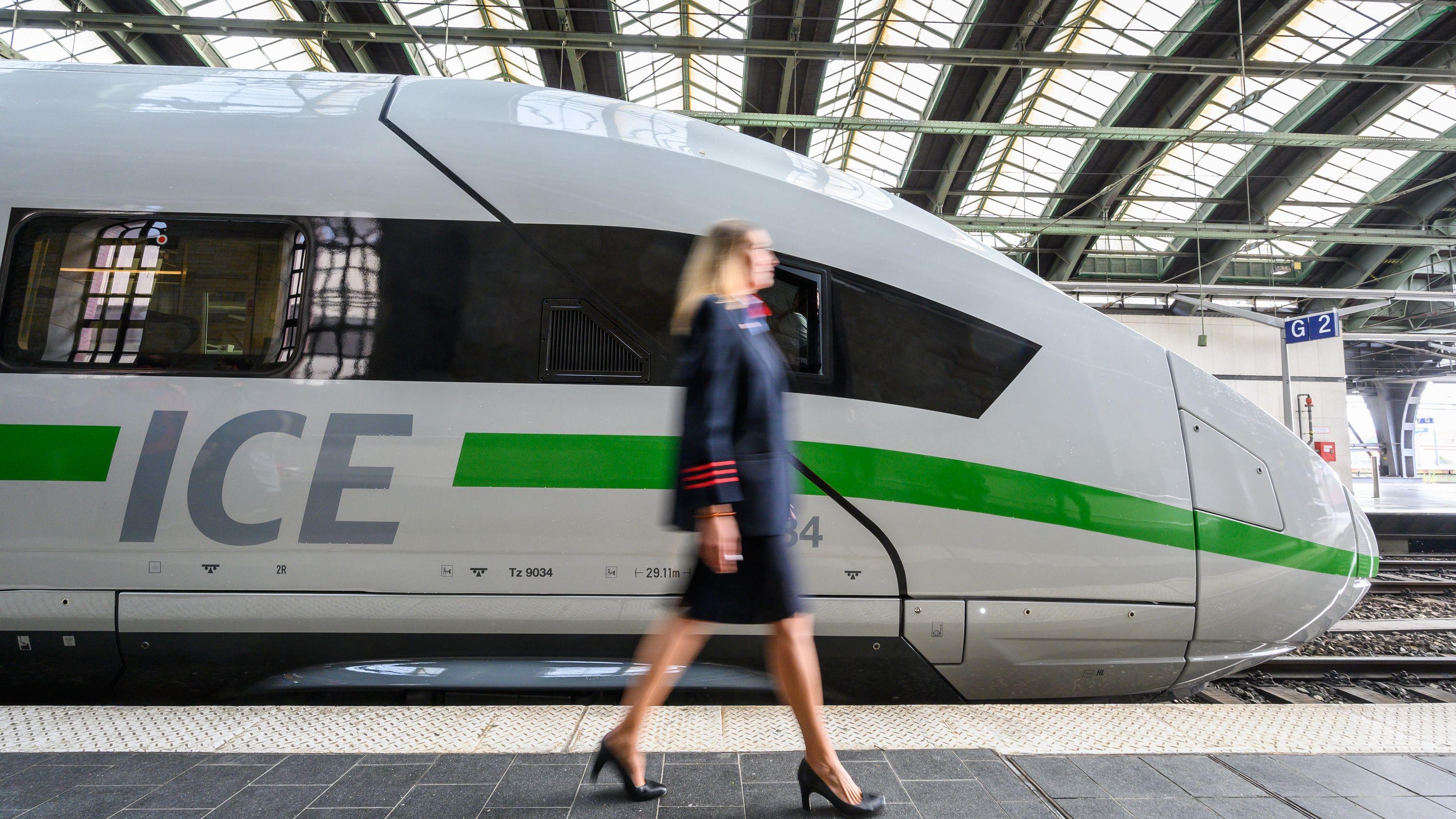 Mitarbeiterin der Deutschen Bahn vor ICE mit neuem Design