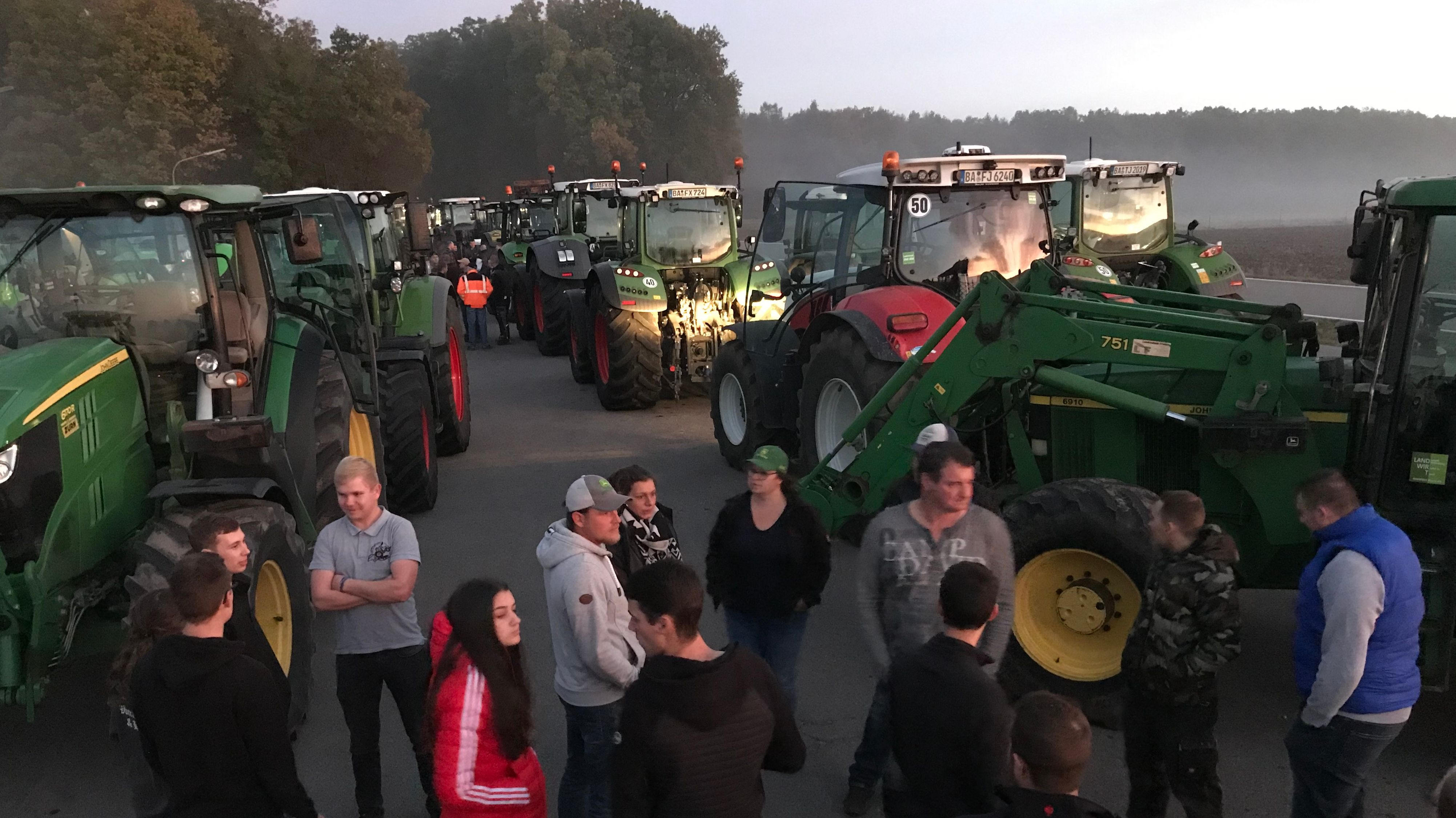 Im Morgengrauen stehen Landwirte vor ihren Traktoren, im Hintergrund Bäume.