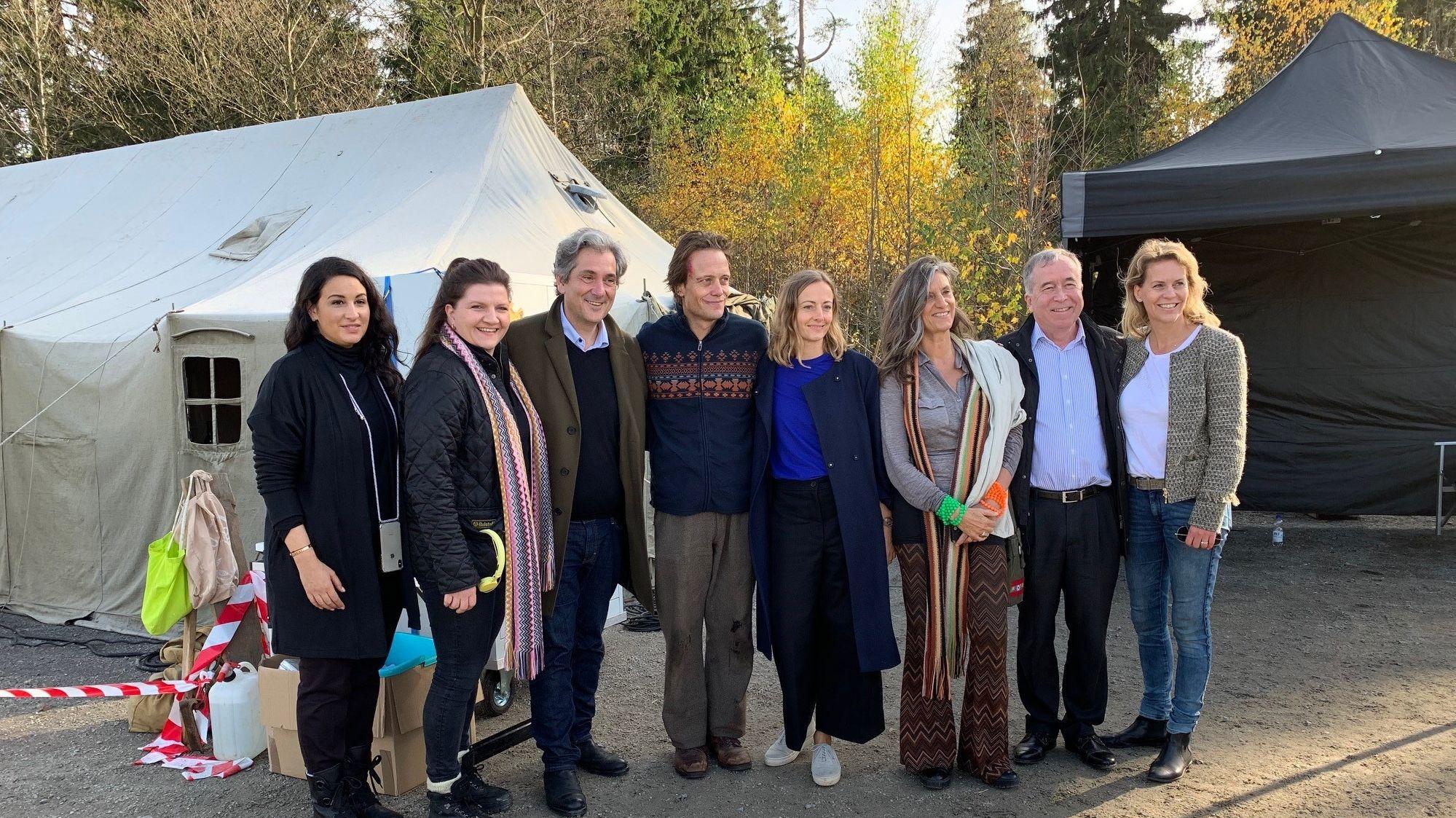 """Vor einem weißen Zelt stehen acht Frauen und Männer, die beim Filmprojekt """"Plan A"""" mitmachen, links im Bild die beiden Produzentinnen Minu Barati und Skady Lis."""