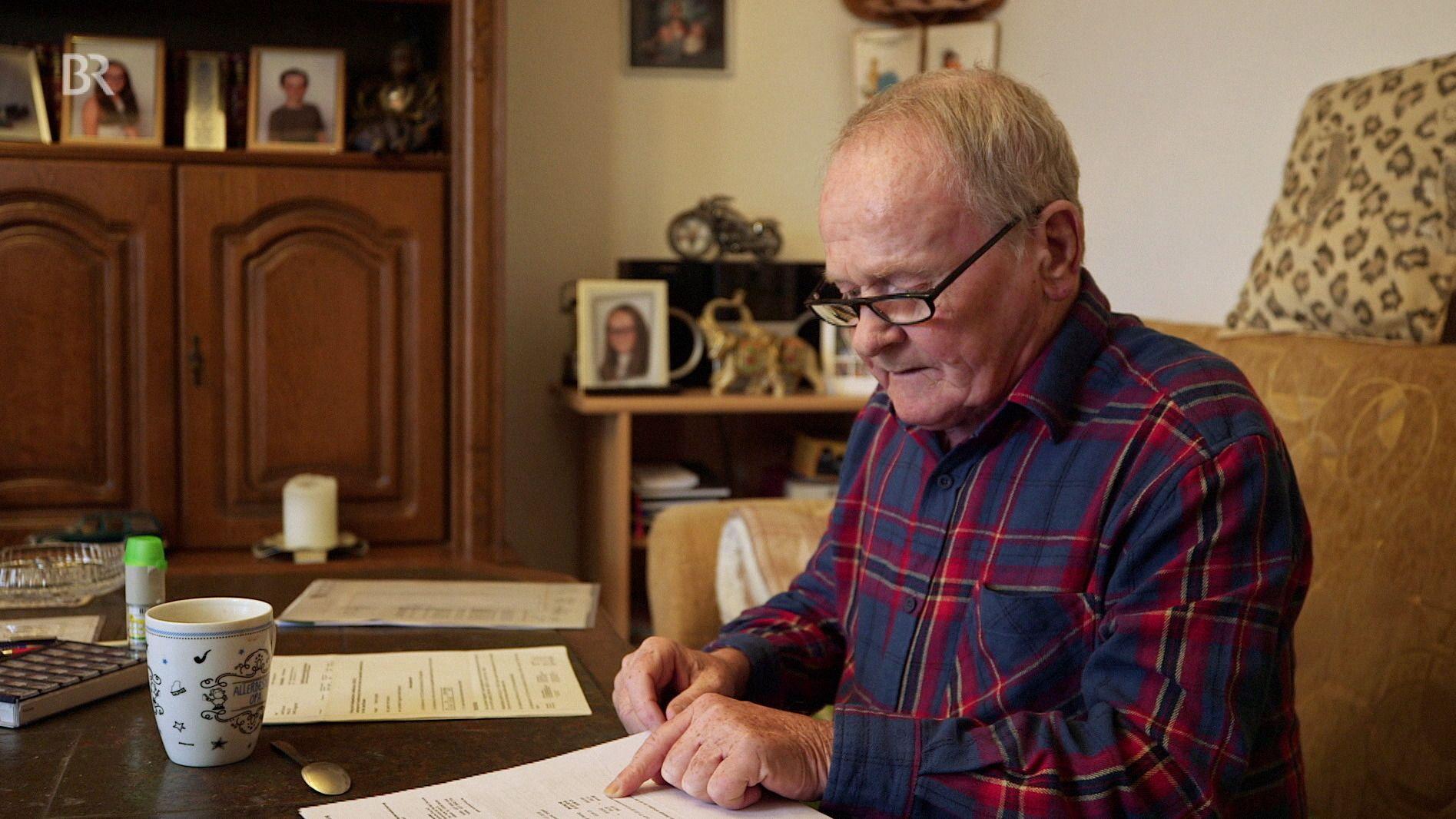 Der Rentner Josef Breuherr sitzt an seinem Wohnzimmertisch und prüft seine Ausgaben