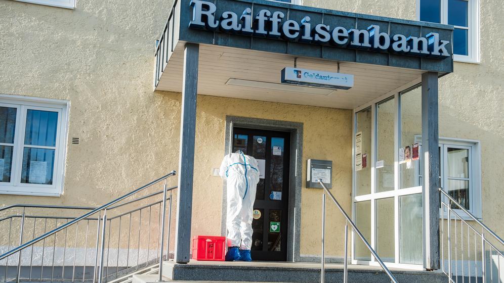 Ein Beamter sucht nach Spuren bei der überfallenen Raiffeisenbank in Obersüßbach   Bild:NEWS5/Pieknik