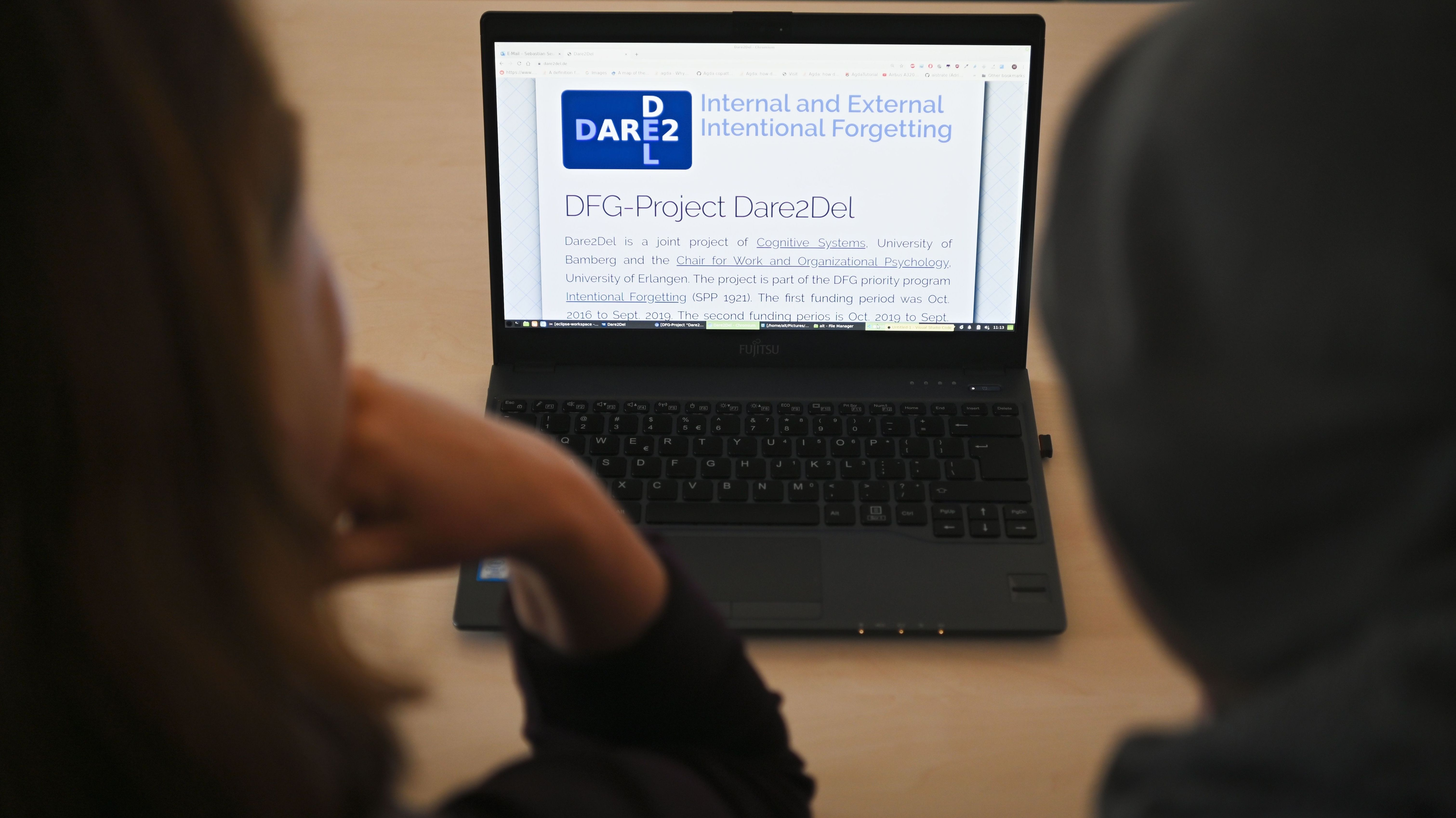 """Zwei Menschen sitzen vor einem Laptop auf dem """"Dare2Del"""" zu lesen ist."""