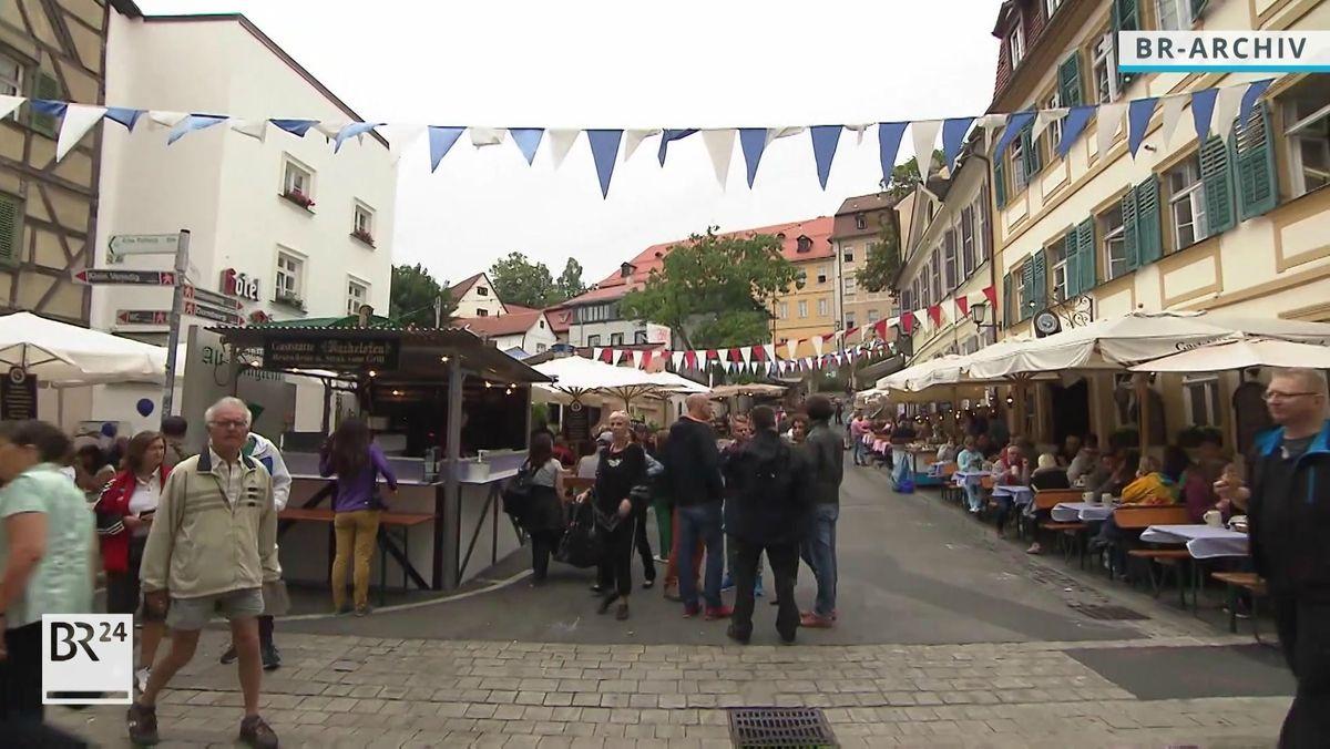 Ein Archivbild zeigt eine Straße in der Bamberger Altstadt mit vielen Leuten, die unter weißen Schirmen auf Bänken sitzen, auf der Straße stehen Buden, und über der Straße sind Bänder mit rot-weißen und weiß-blauen Wimpeln gespannt.