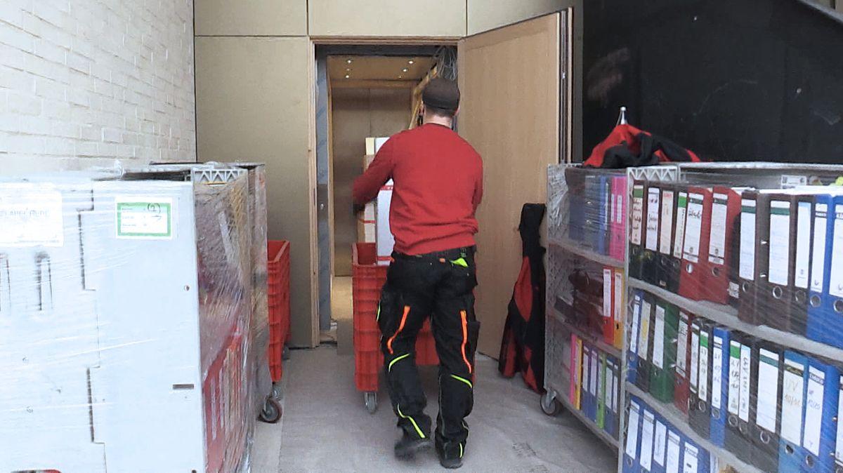 Ein Möbelpacker fährt einen Rollcontainer vorbei an Rollregalen mit Aktenordnern.