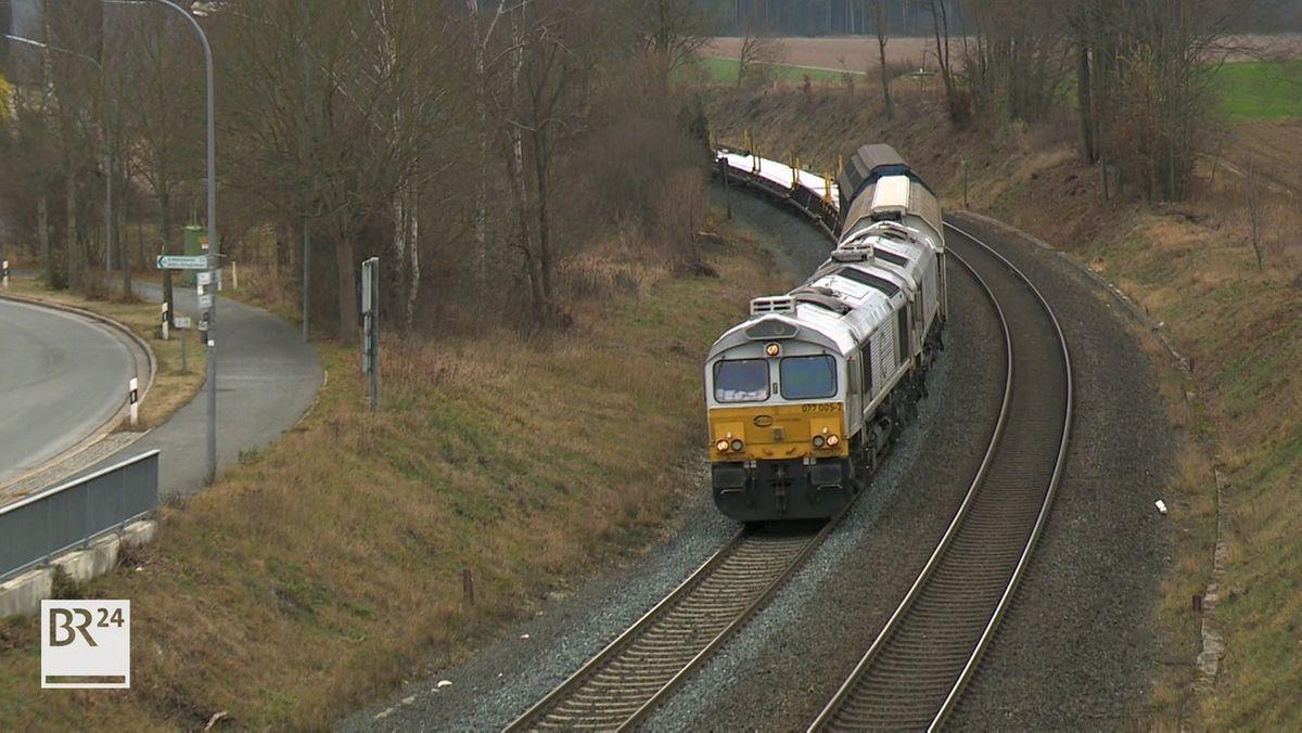 Ein Zug fährt auf einer nicht elektrifizierten Strecke in Richtung Bahnhof Martinlamitz, im Hintergrund eine Straße und Bäume.