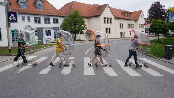 Vier Menschen schieben Einkaufswagen über einen Zebrastreifen, die mit Schutzfolien ausgestattet sind.