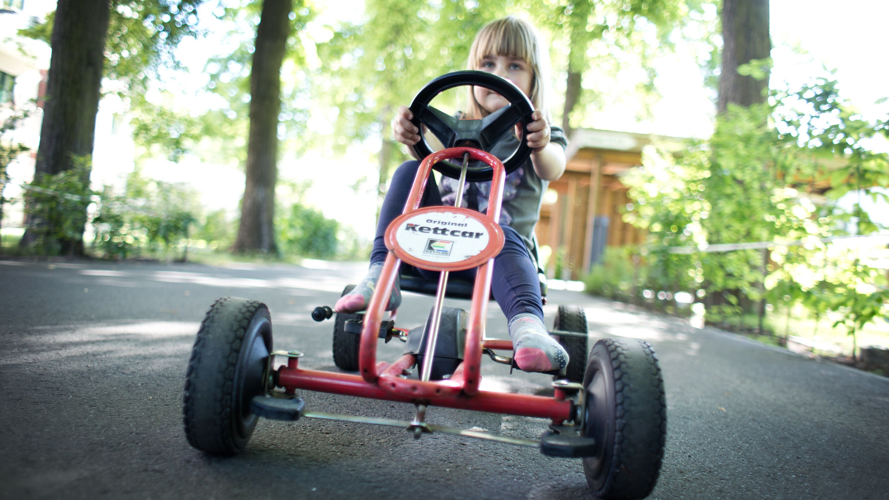 Ein Mädchen fährt auf einem Kettcar.
