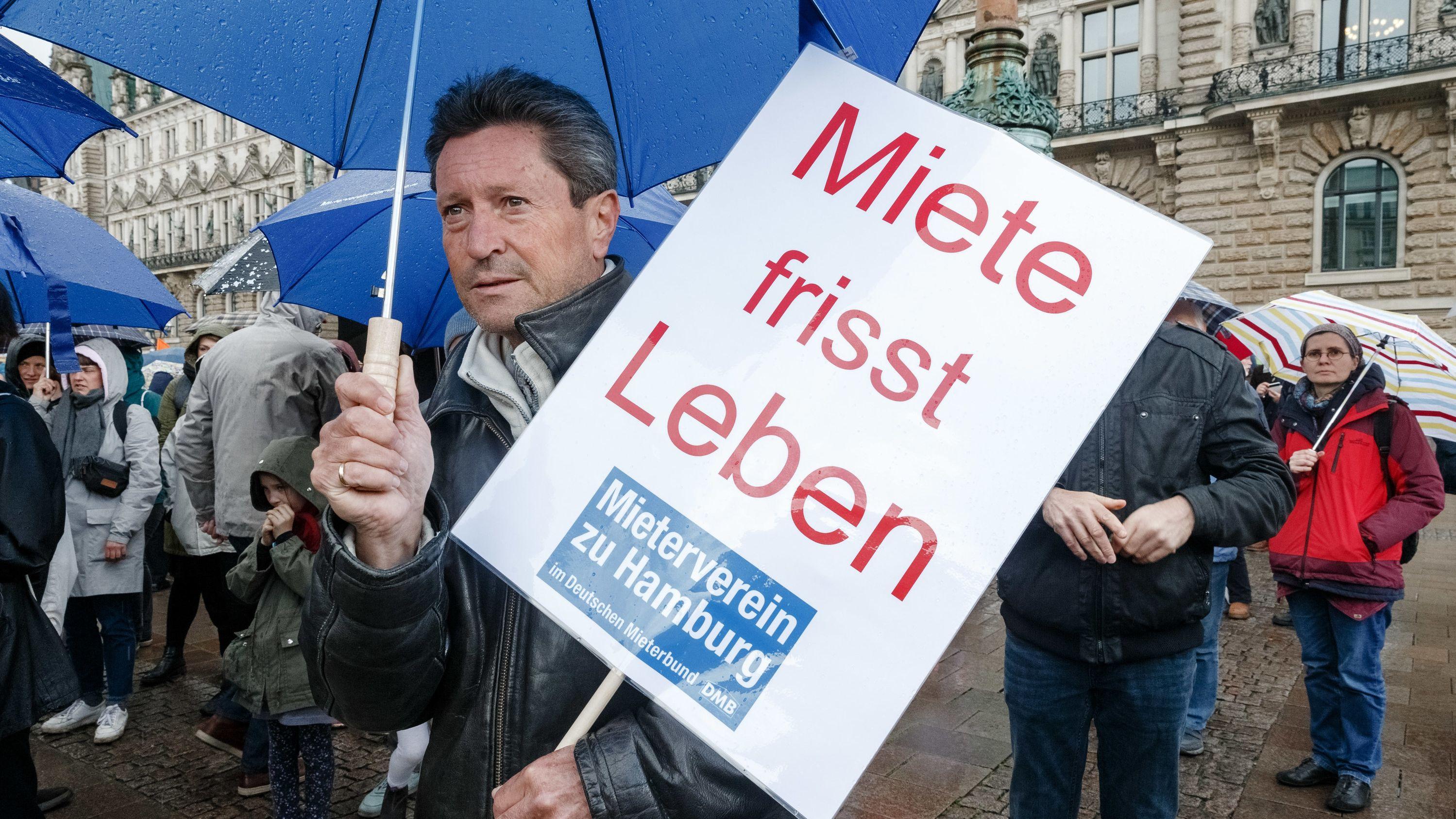 """Bei einer Demonstration gegen die hohen Mietpreise hält ein Mann ein Plakat mit der Aufschrift: """"Miete frisst Leben""""."""