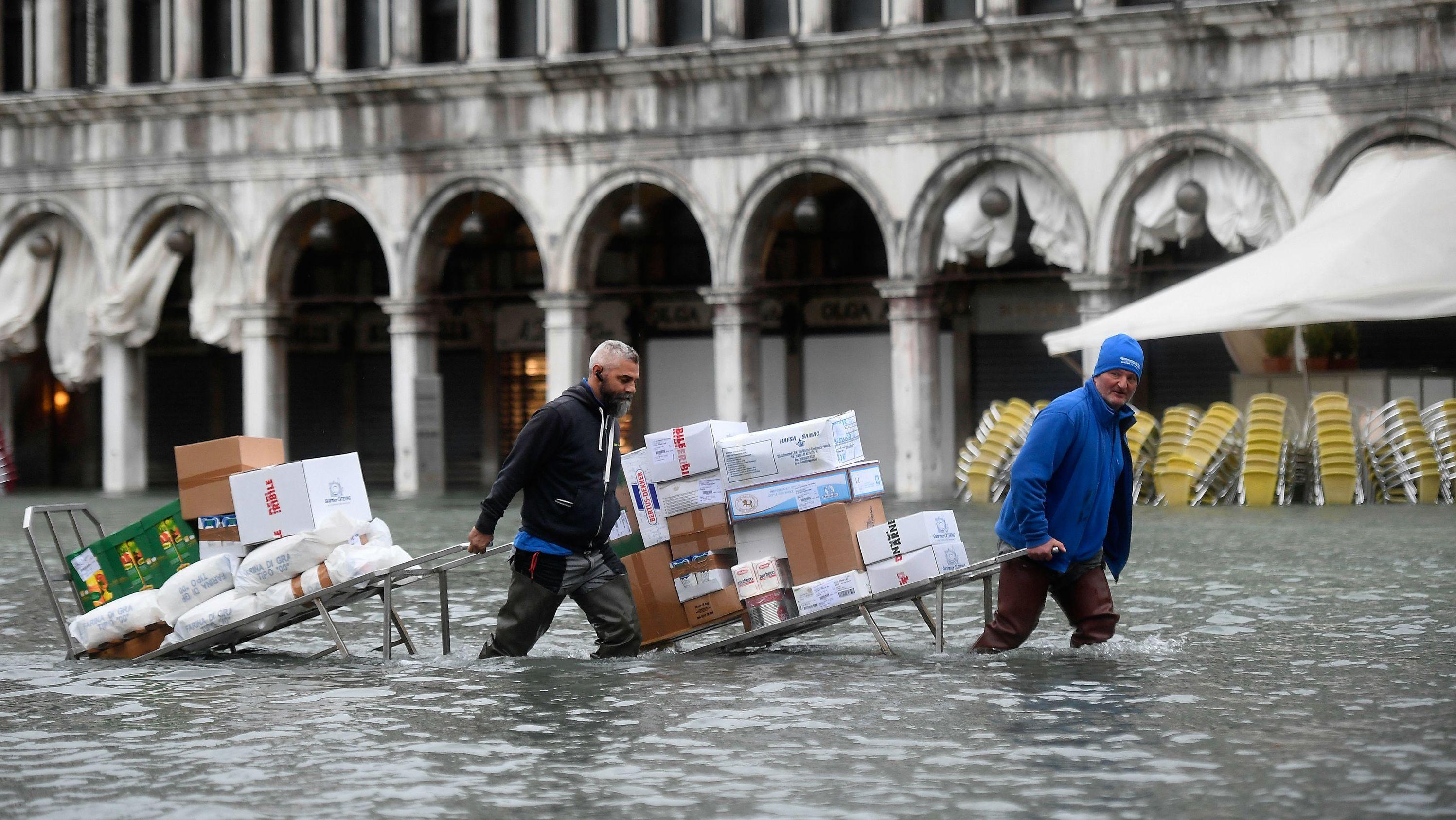 Venedig: Männer waten mit Kartons und Lebensmitteln, die sie auf einer Trage transportieren, durch das Hochwasser auf einem überfluteten Platz.