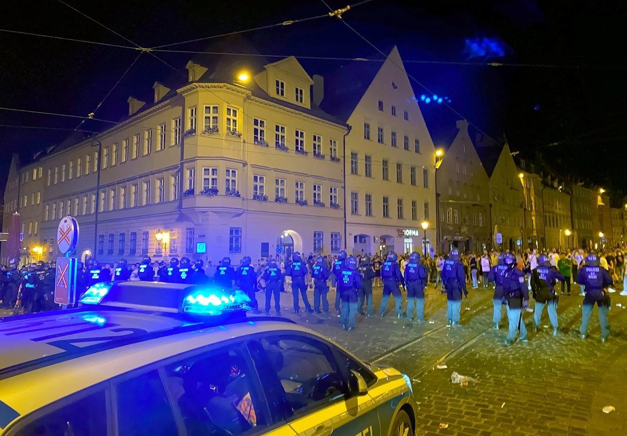 19.06.2020, Bayern, Augsburg: Polizisten stehen an einem Platz in der Innenstadt, wo sich Menschen zum Feiern versammelt haben. Die Polizei hat in der Nacht zuSonntag eine Ansammlung von hundertenFeiernden aufgelöst. Bei dem Einsatz seien zahlreiche Beamte verletzt worden, sagte ein Polizeisprecher.Auch auf der Seite der Feiernden habe es Verletzte beidemEinsatz gegeben. (zu dpa: «Wieder Outdoor-Partys und Krawall in Bayern») Foto: Andreas Herz/dpa +++ dpa-Bildfunk +++
