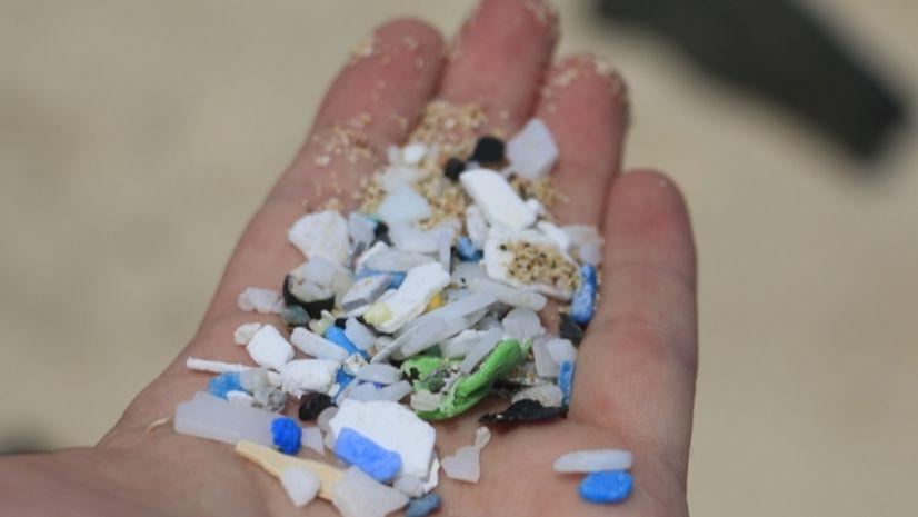 Eine Hand hält kleine Plastikpartikel.