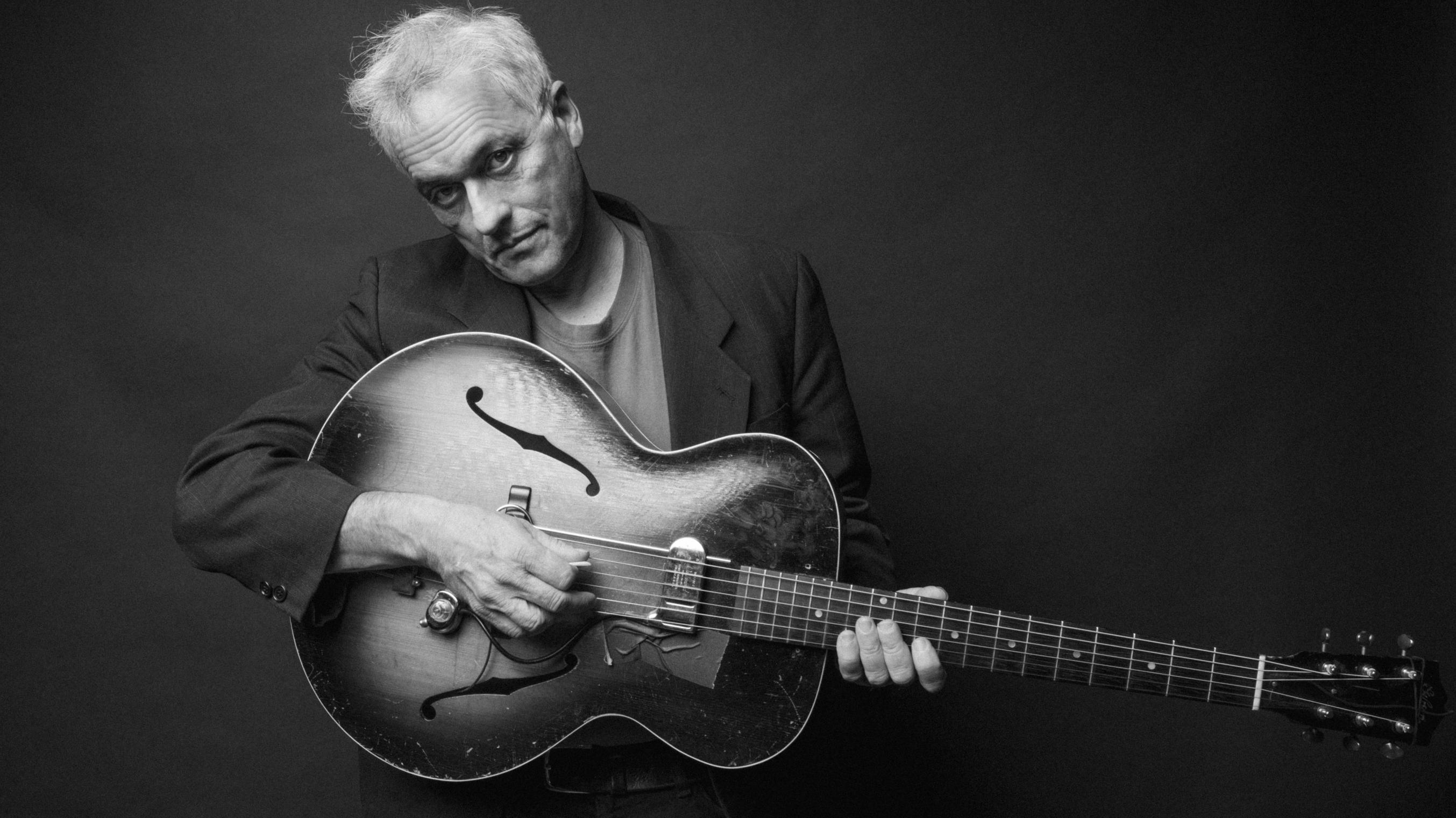 Marc Ribot in schwarz weiß hält eine Gitarre in der Hand