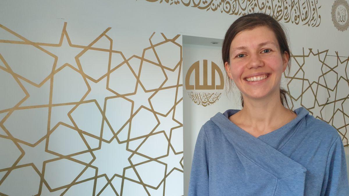 Eine Frau steht in einer Moschee vor einer Wand mit orientalischen Mustern.