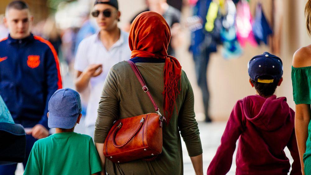 Frau mit Kopftuch und Kindern an der Hand in der Fußgängerzone in München