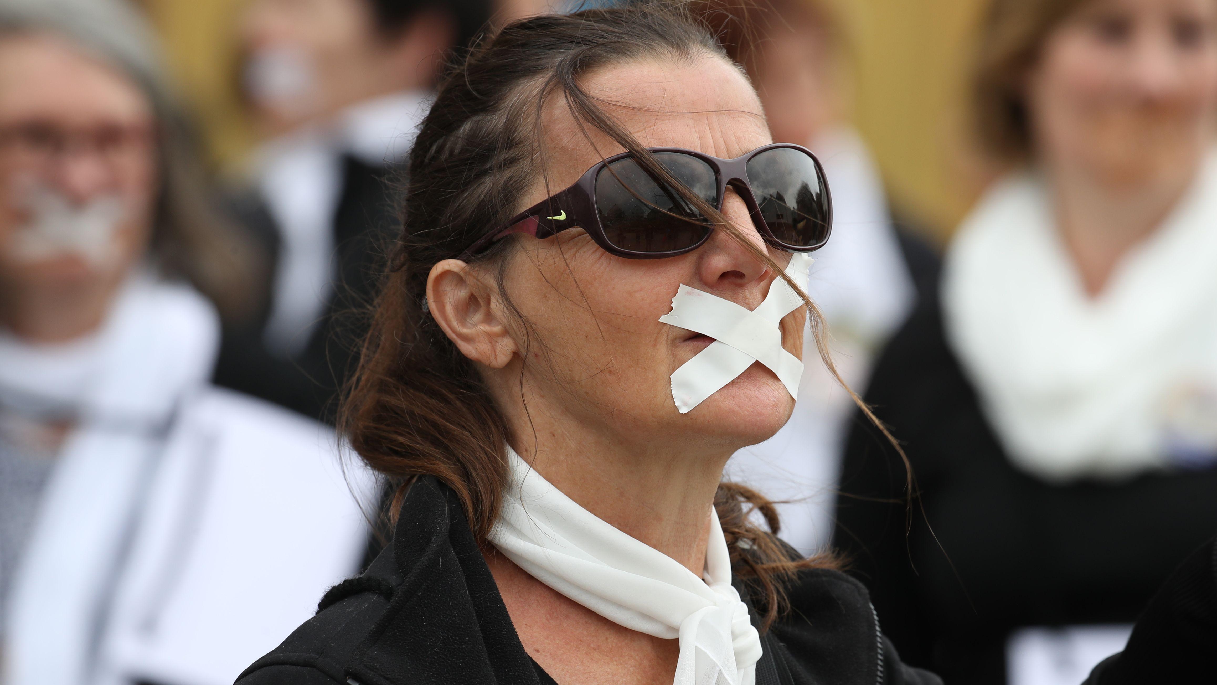 Frau demonstriert mit Pflaster über dem Mund und weißem Schal um den Hals gegen die rein männlichen Machtstrukturen in der katholischen Kirche