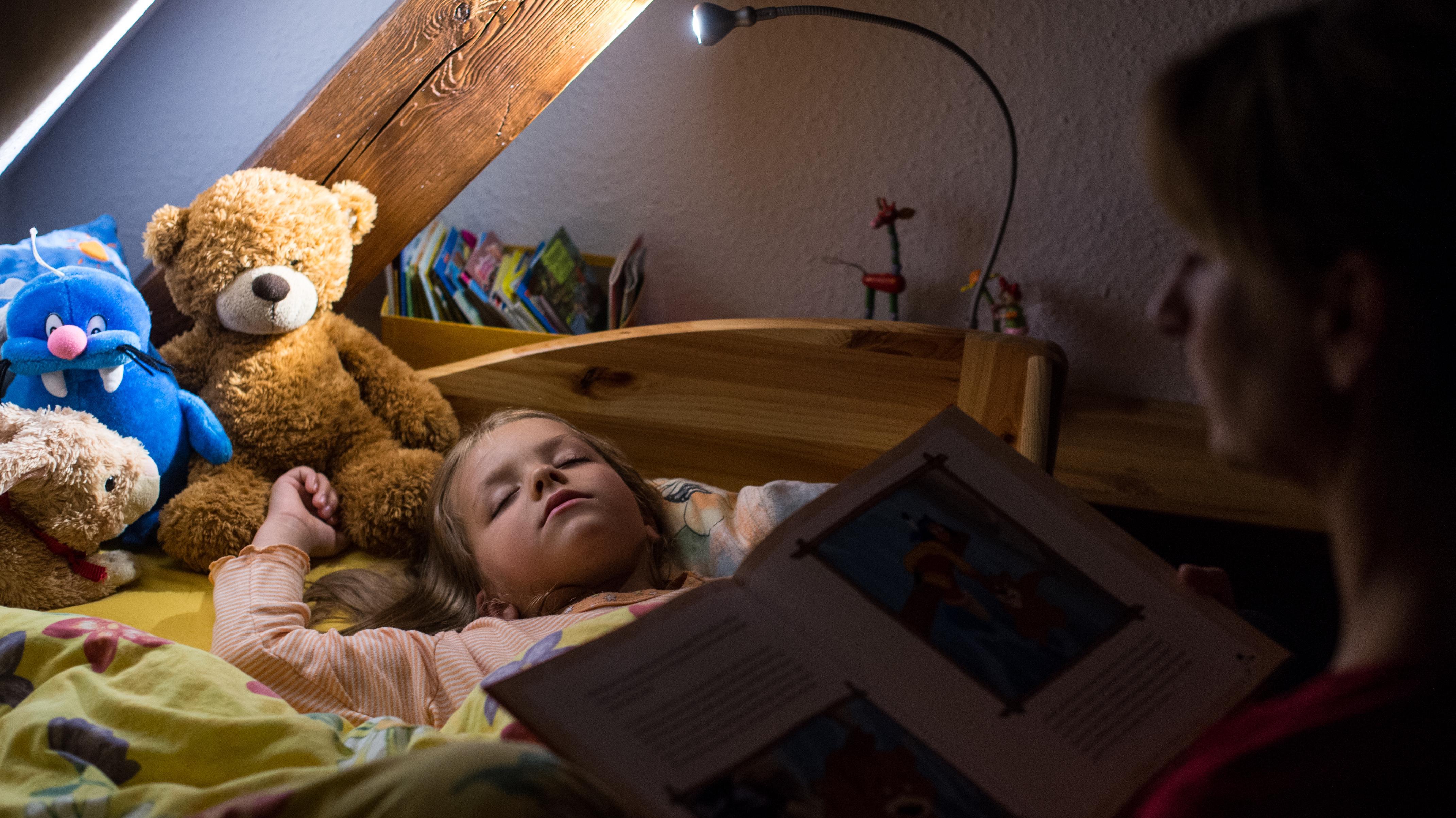 Ein fünfjähriges Mädchen ist beim Vorlesen einer Gute-Nacht-Geschichte eingeschlafen.