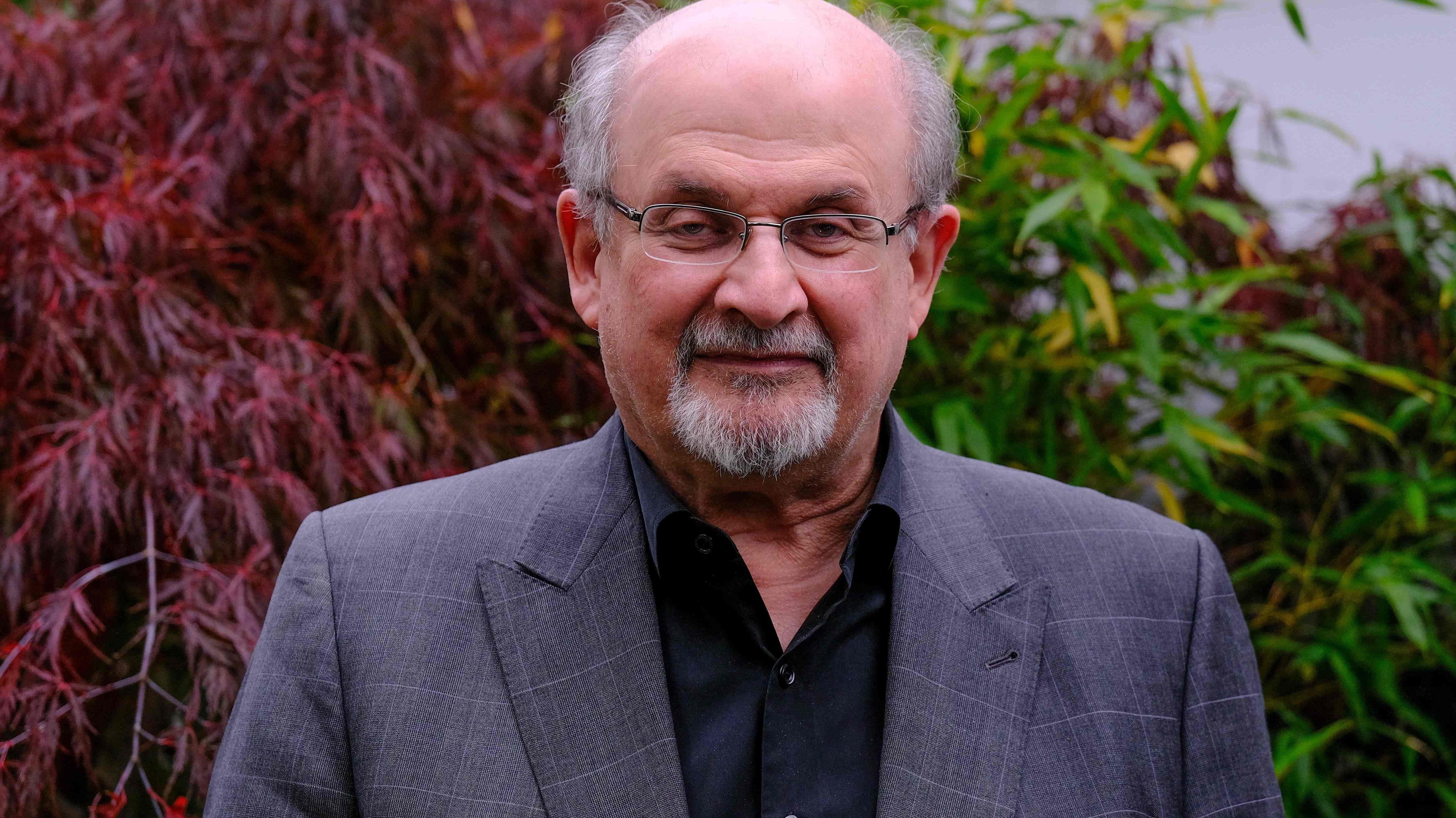 Salman Rushdie im Anzug vor einer Kulisse aus tief roten und grünen Sträuchern