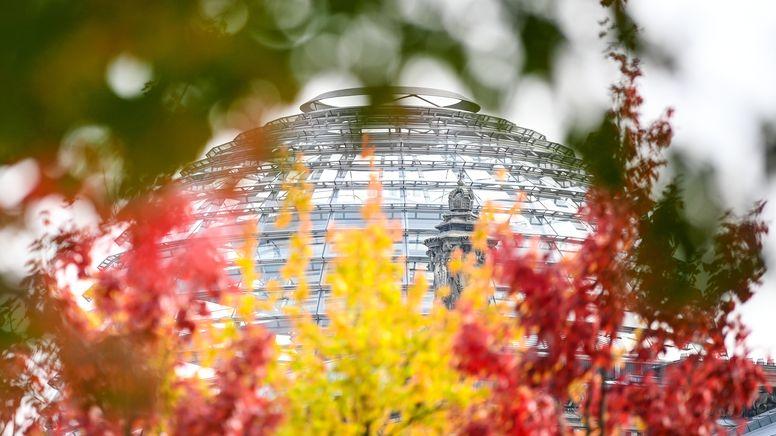 Rot-gelb-grün herbstlich verfärbte Blätter an Bäumen vor der Reichstagskuppel    Bild:pa/dpa/Britta Pedersen